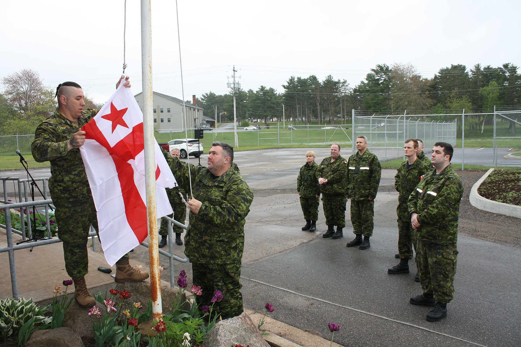 Two men wearing disruptive pattern uniforms prepare to raise a red and white flag; eight similarly-dressed people watch.