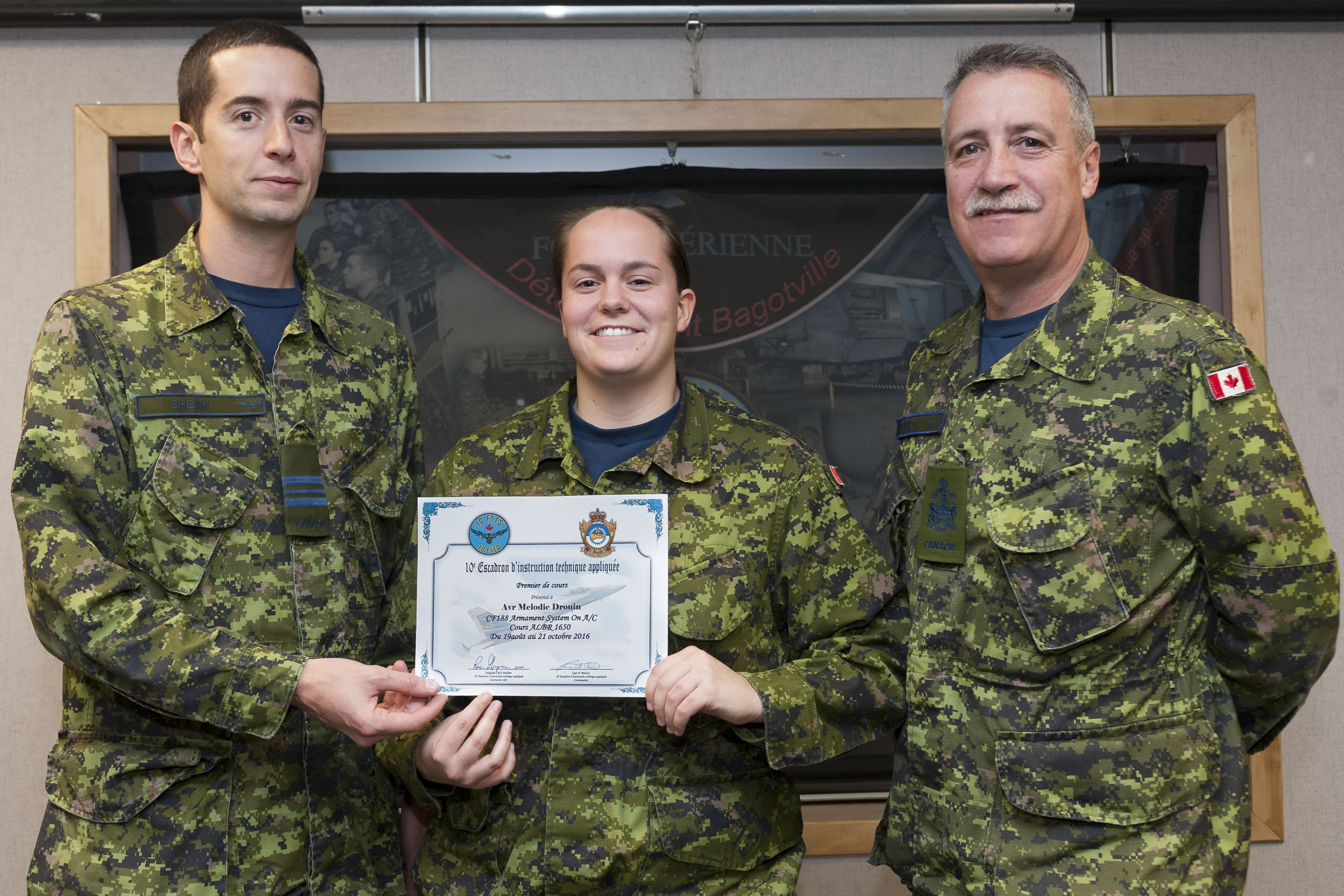 Aviator Mélodie Drouin receives her certificate of graduation from the CF-18 weapons technician course from Major Christian Sheink (left), maintenance officer at 433 Tactical Fighter Squadron at 3 Wing Bagotville, Quebec, and Chief Warrant Officer Simon Beaulieu, the squadron's chief warrant officer. PHOTO: Corporal Karine Chalifour, BN14-2016-0594-001