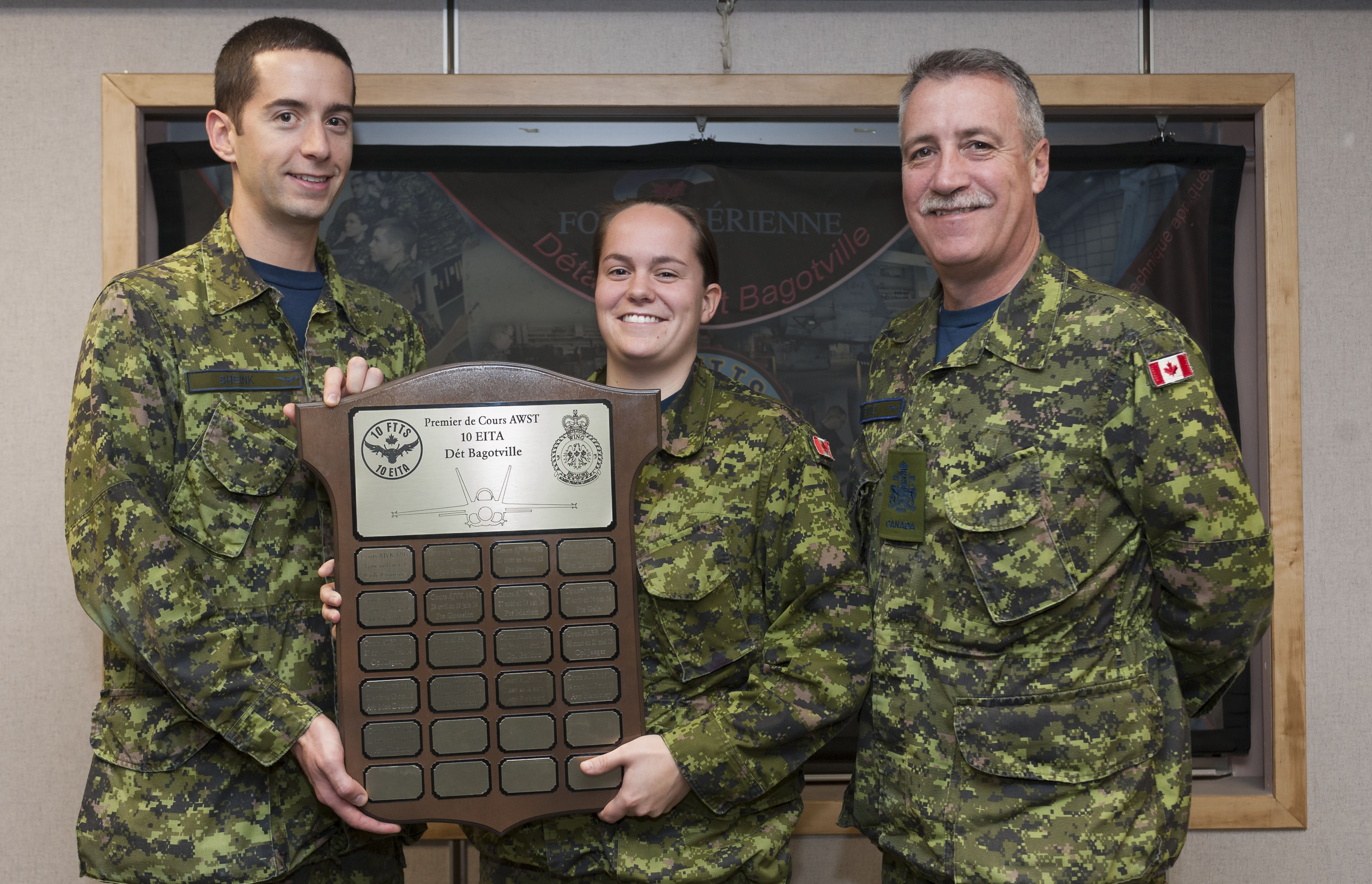 Two men and a woman, dressed in green disruptive pattern combat uniforms, look into the camera. The man on the left and the woman in the centre hold a large wooden plaque that has small engraved brass plaques attached to it.