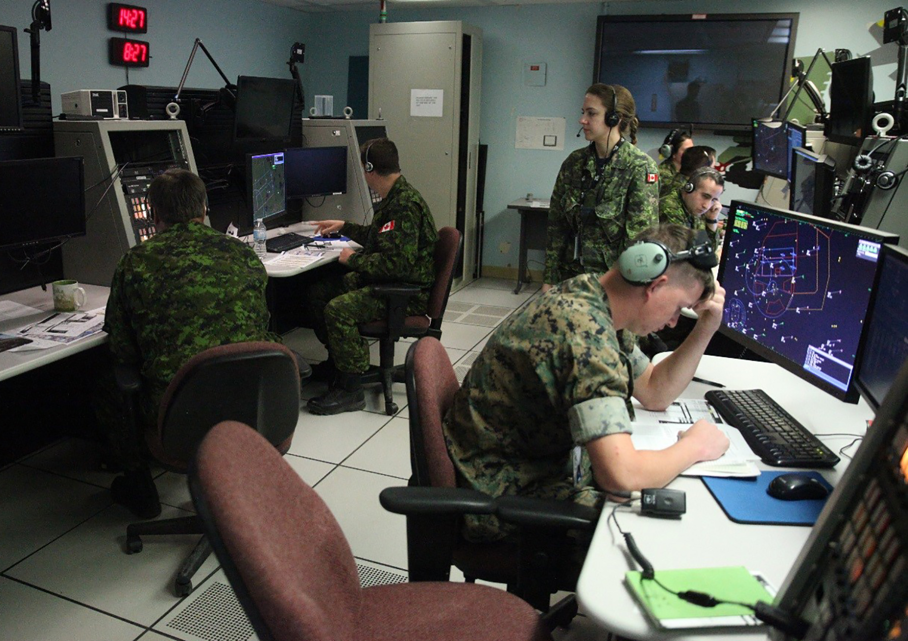 Men and women in disruptive pattern uniforms work at computer stations in a control room.