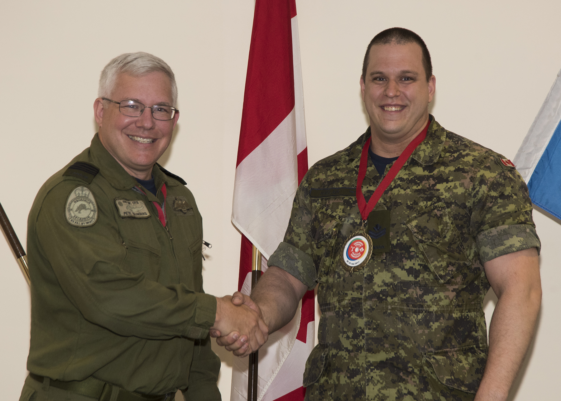 A man in an olive green uniform shakes hands with a man wearing a green and black disruptive pattern uniform and a medal around his neck.