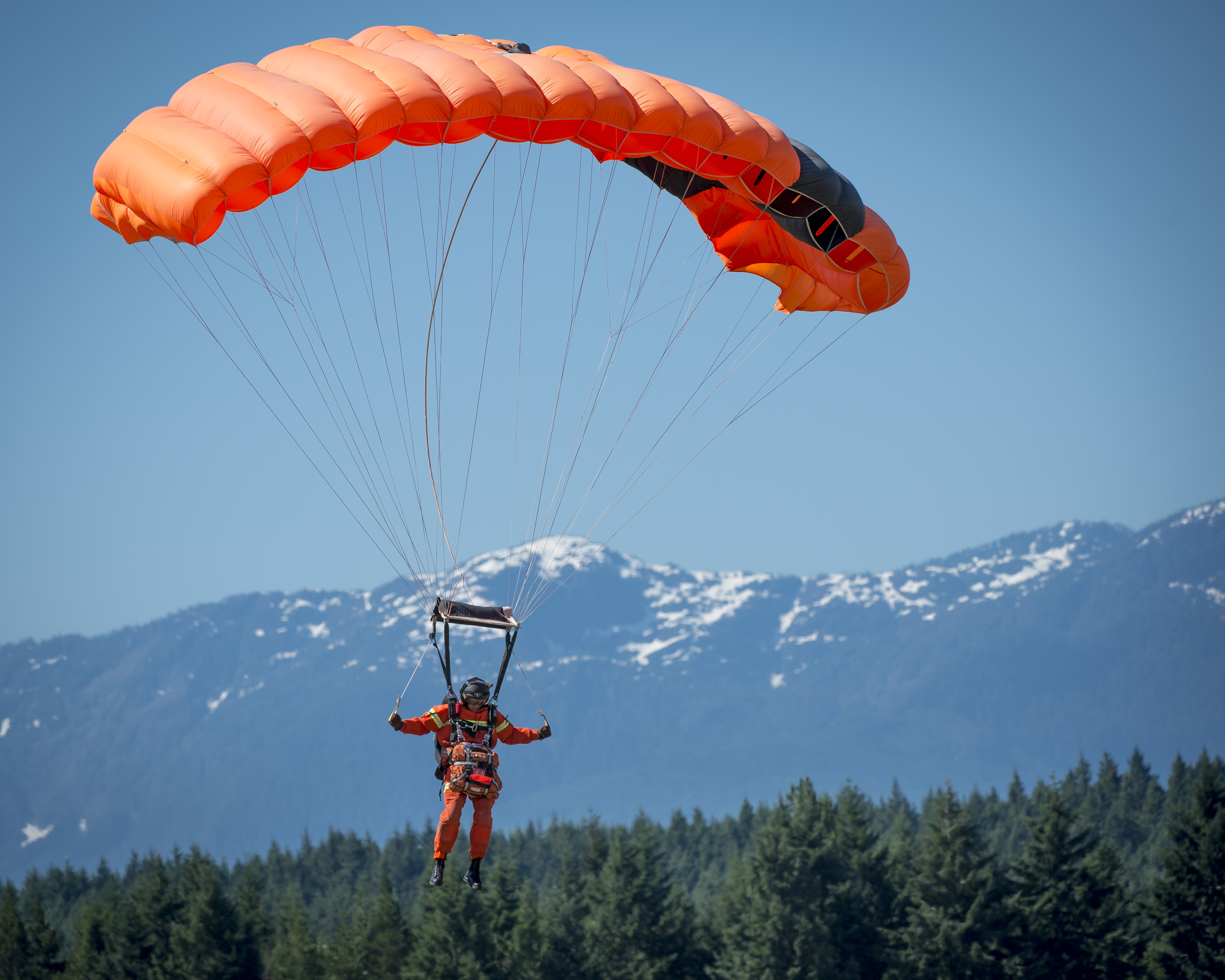 A person in a bright orange jumps suit is suspended in the air from an orange rectangular parachute. A range of snow-topped mountains is in the background.