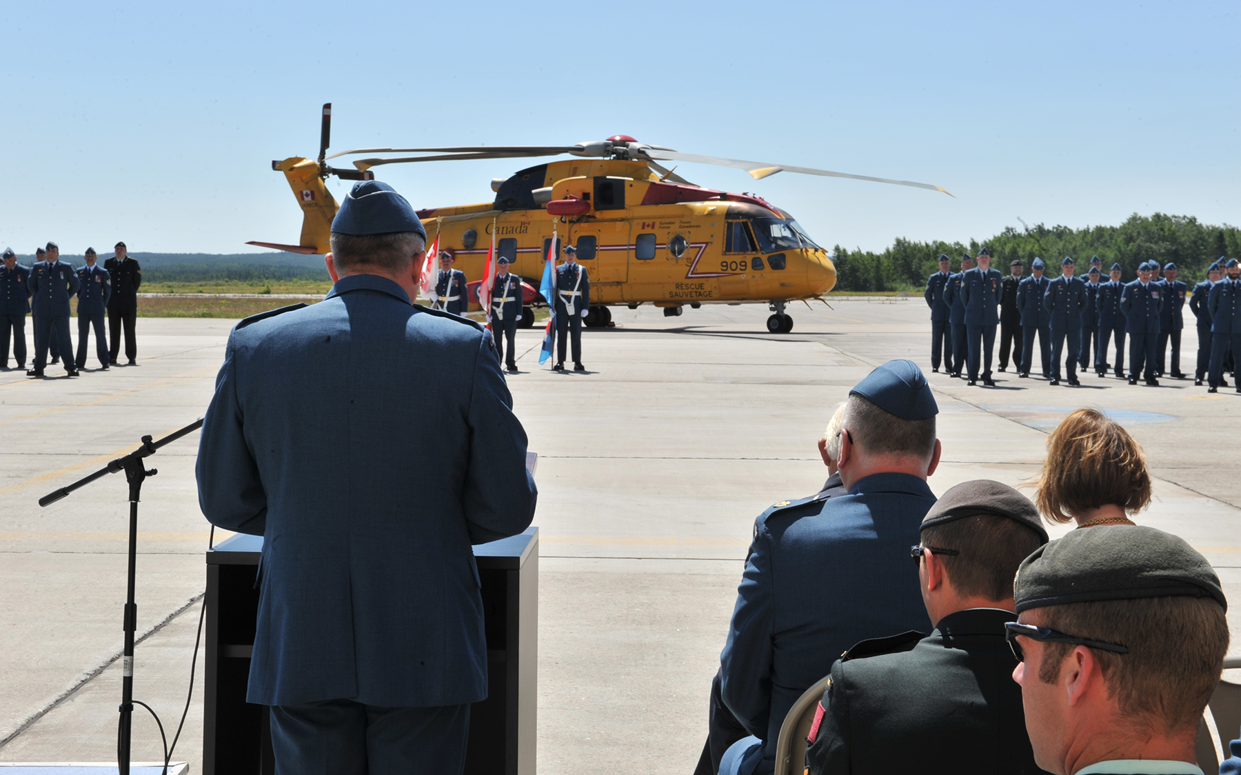 "Major-General Christian Drouin (left front) addresses the gathering during the Change of Command ceremony held on July 18, 2017, at 9 Wing Gander, Newfoundland and Labrador, to mark the ""passing of the torch"" from Colonel Pierre Haché to Lieutenant-Colonel Jenn Weissenborn. PHOTO: Second Lieutenant Todd Silk"