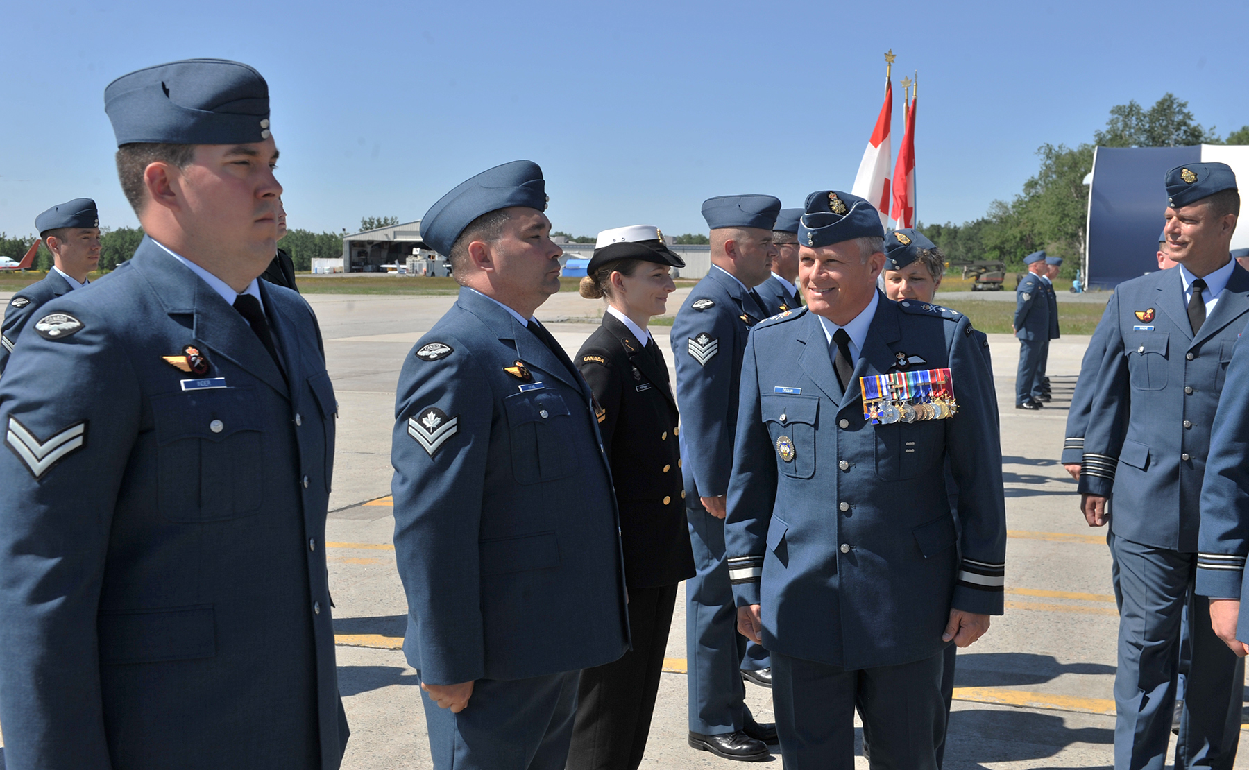 During the July 18, 2017, Change of Command ceremony held at 9 Wing Gander, Newfoundland and Labrador, Major General Christian Drouin (centre), accompanied by LS Ewa Portman and MCpl Scott Leckie, inspects the troops, including Cpl Paul Inder. PHOTO: Second Lieutenant Todd Silk