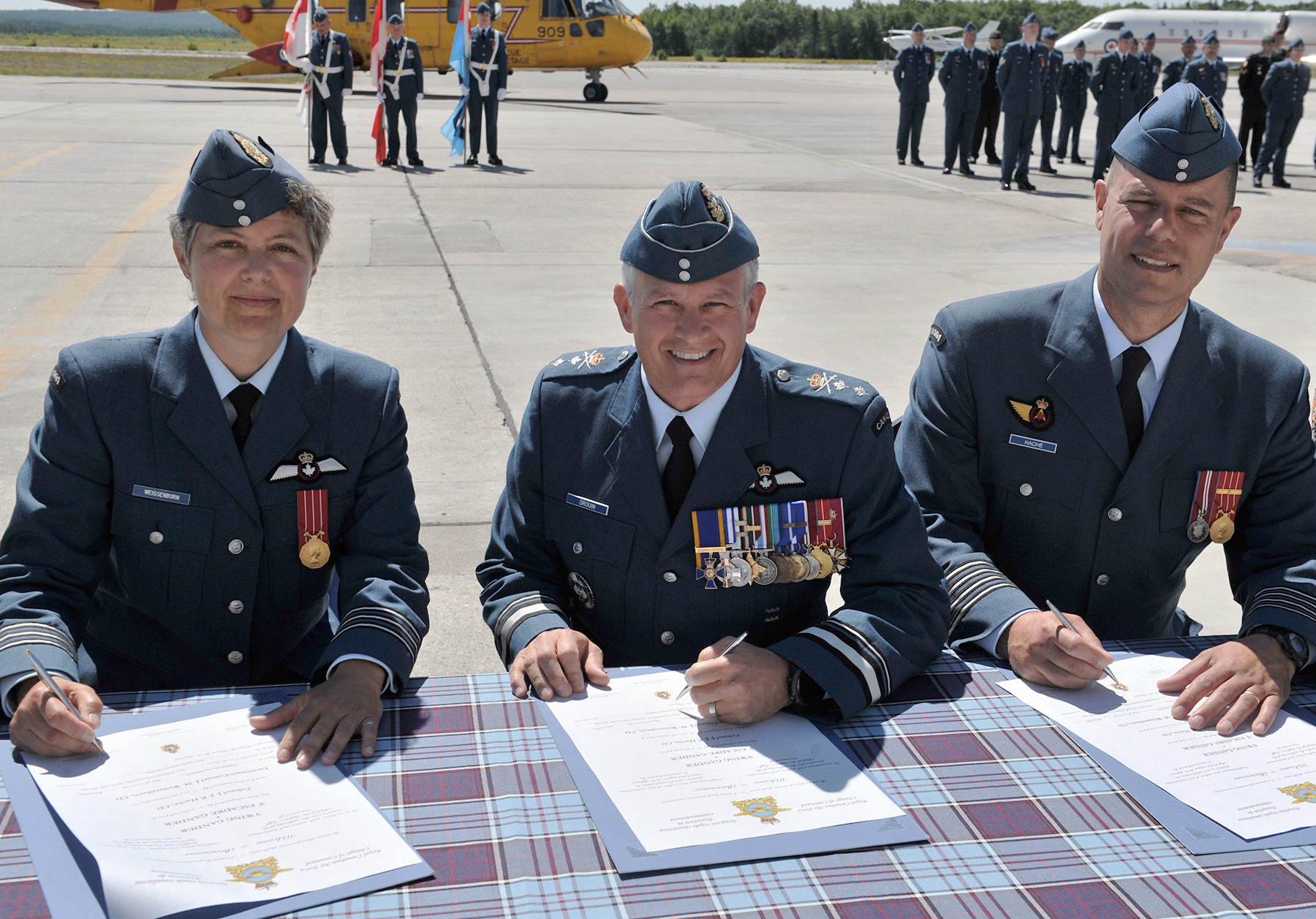 A woman and two men with pens in hand and documents in front of them sit outdoors at a table covered with a tartan cloth. Behand the three are aircraft, and people in uniforms, including three flag-bearers.