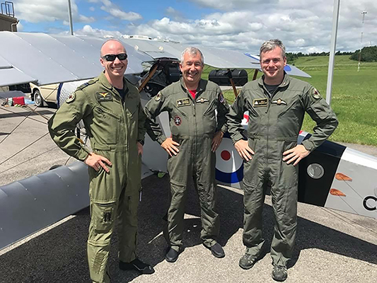 Three men in olive green flight suits stand beside a vintage bi-plane covered in silver-grey fabric and bearing the First World War-era rondel of the Royal Flying Corps.