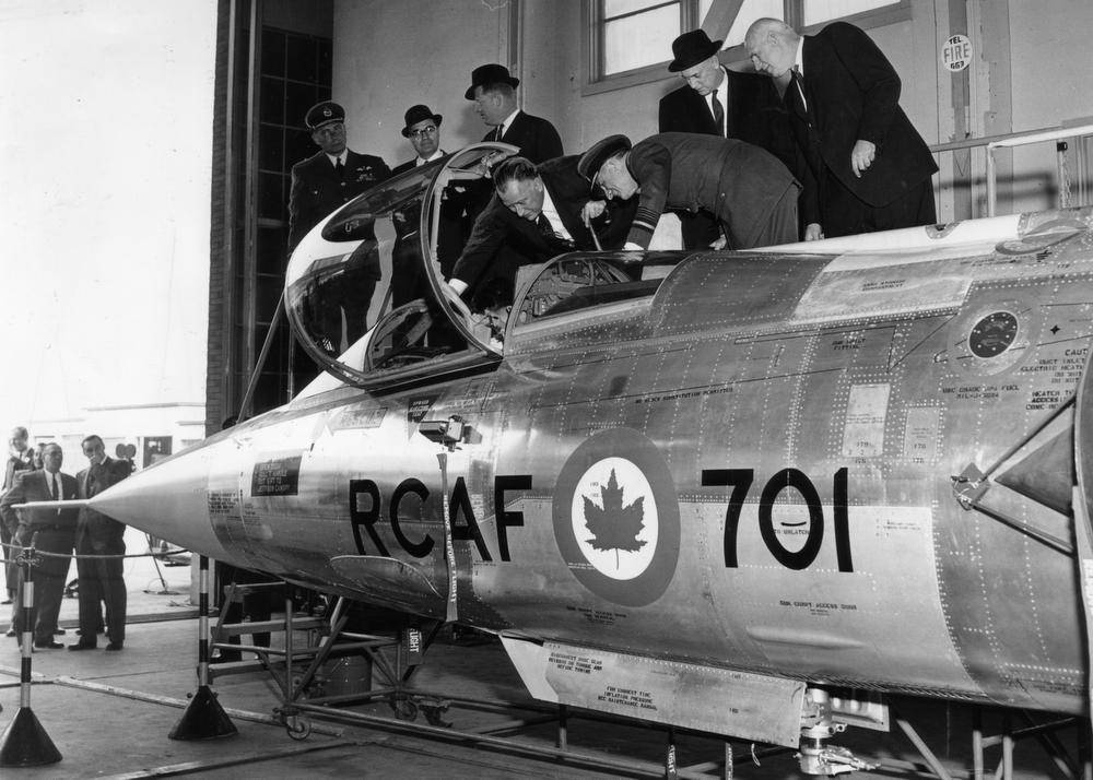 Assisted by two RCAF officers, a group of civilian dignitaries examine CF-104 Starfighter No. 701 in an undated black and white photograph. PHOTO: DND