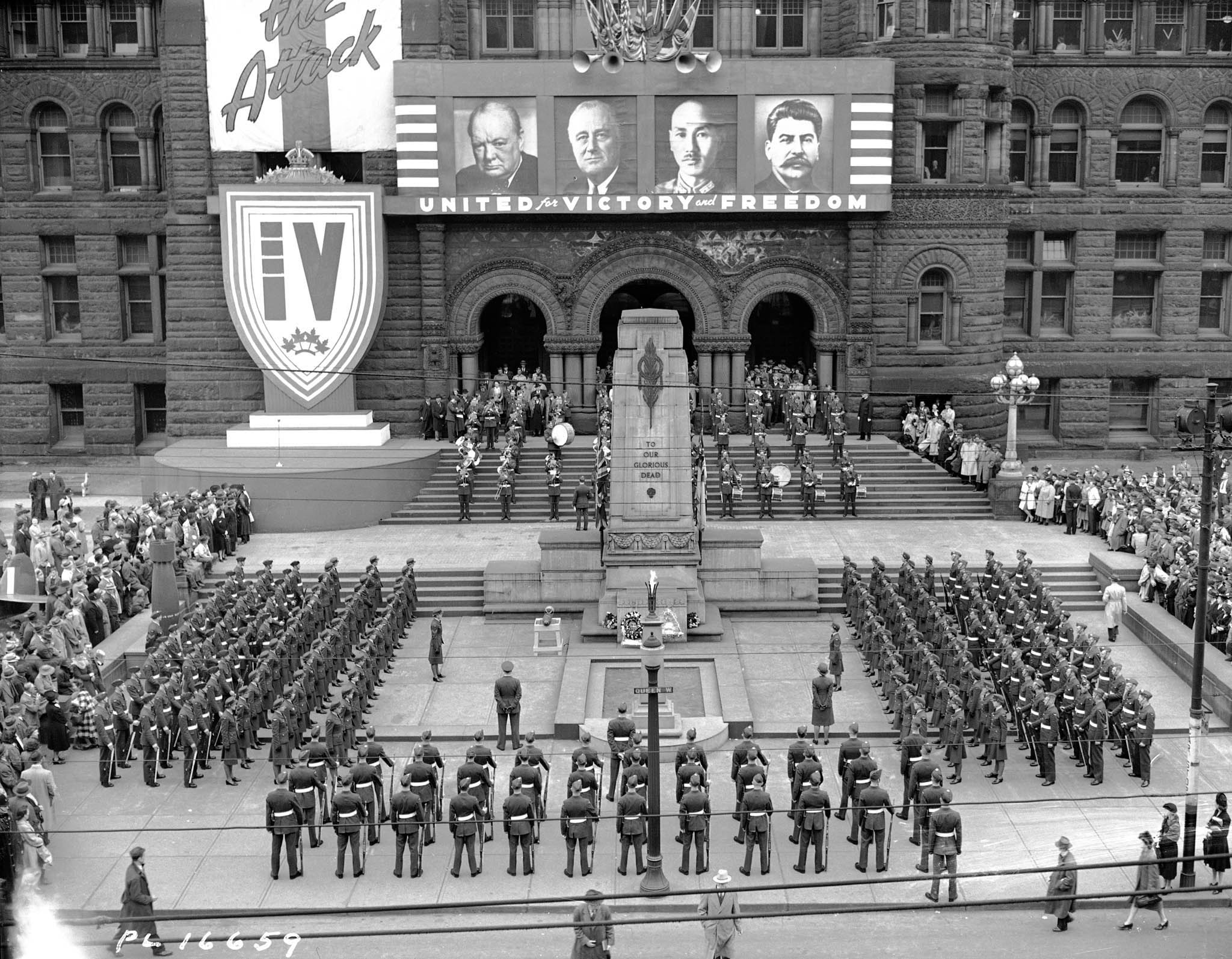 "A black and white photograph of a large, old stone building, and a U-shaped formation of uniformed men and women standing beside and at the foot of a memorial that reads, ""To our glorious dead""."