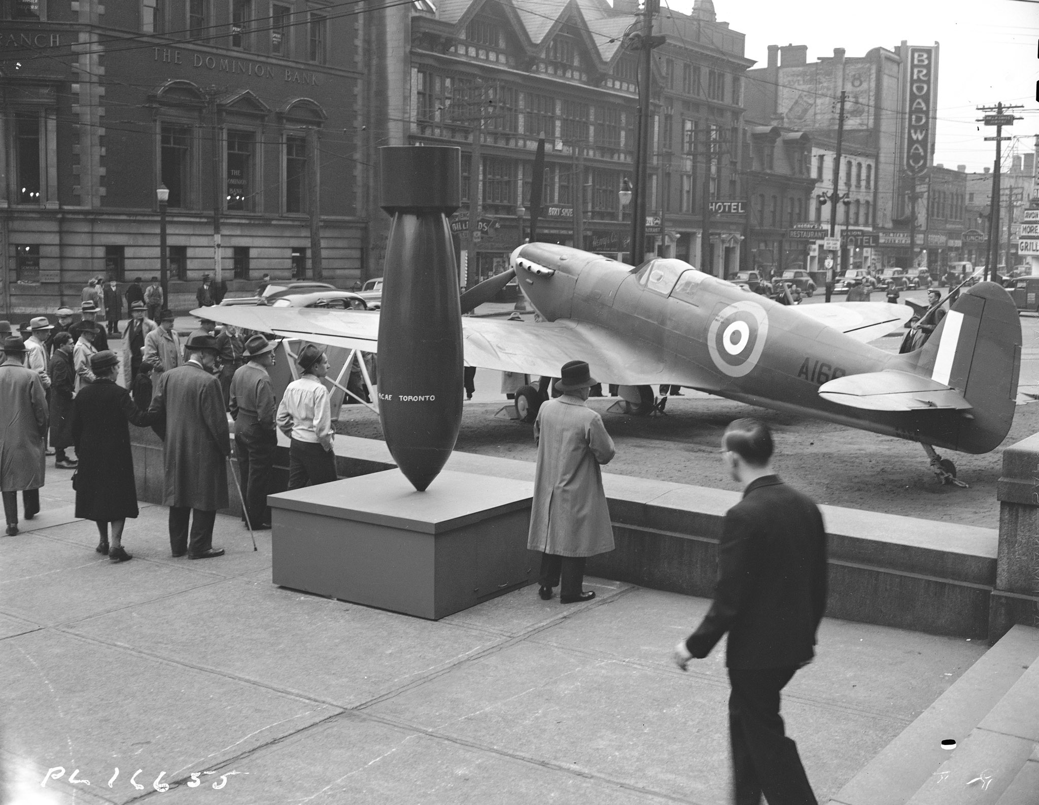 "A Royal Canadian Air Force Spitfire draws admirers in downtown Toronto on May 10, 1943. The fighter aircraft, along with an enormous bomb labelled ""RCAF Toronto"", were on display as part of Air Force Week in the city. PHOTO: DND Archives, PL-16655"