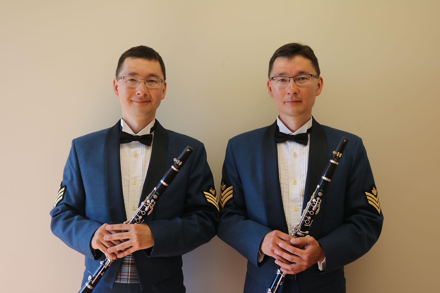 Two men who look alike, wearing blue uniforms, stand and hold a clarinet each.