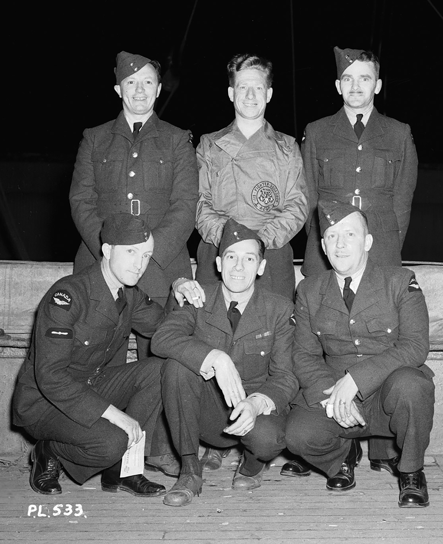While groundcrew kept the aircraft of No. 1 Fighter Squadron fueled, these squadron cooks kept the aircrew and groundcrew fueled. Front row, from left: Leading Aircraftman W.J. Hyndman (Calgary, Alberta), Aircraftman First Class J. J. Davis (Owen Sound, Ontario), and Aircraftman First Class A. Jensen (Vancouver, British Columbia). Back row, from left: Aircraftman First Class J.H. Greer (Montreal, Québec), Aircraftman First Class J. Gallagher (Montreal, Québec), and Aircraftman First Class G.F. McGeragle (Vancouver, British Columbia). PHOTO: DND Archives, PL-533