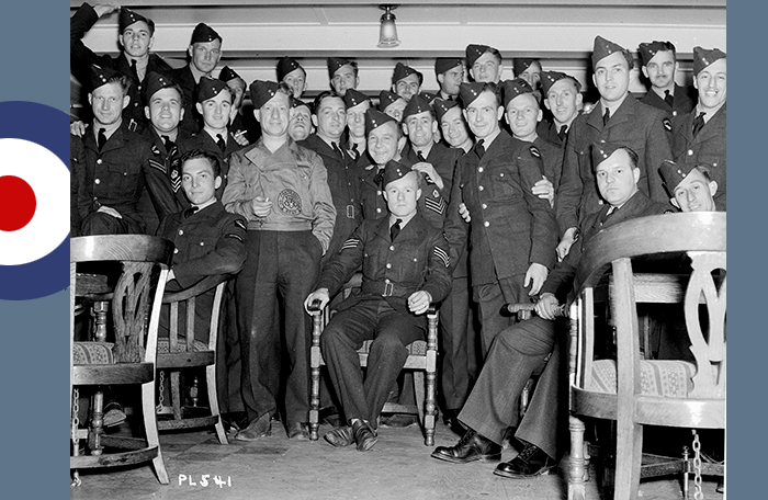 slide - Thirty uniformed men gather for a photograph in a low-ceilinged room.