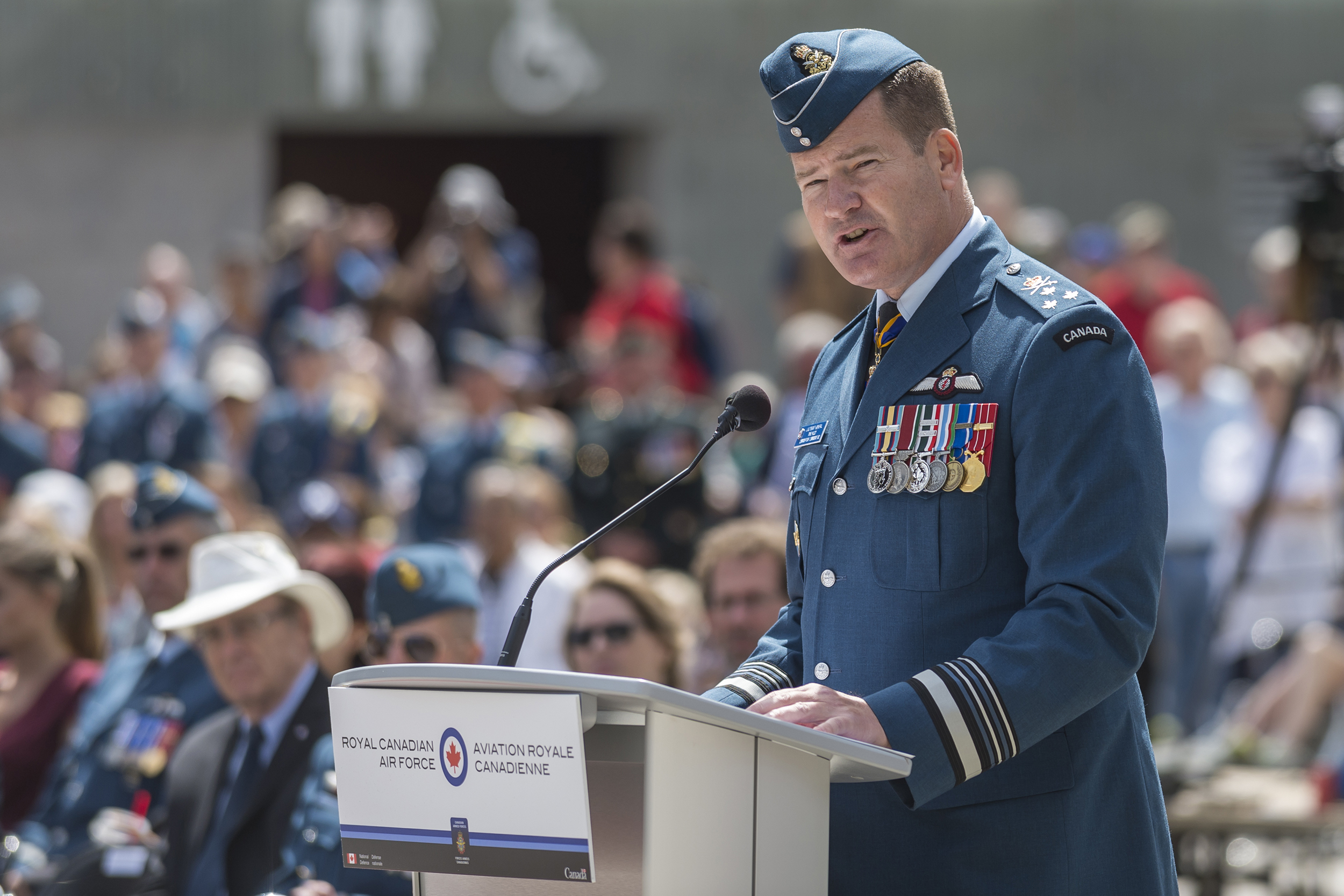 A man in a blue uniform stands behind a podium, speaking.
