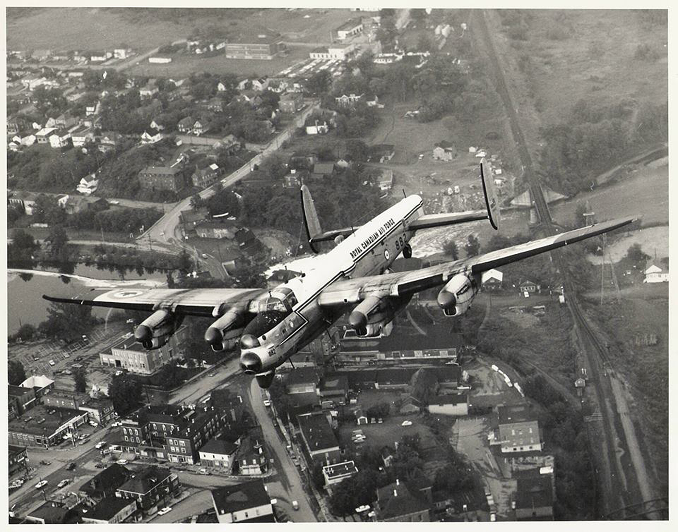 A black and white photo of a large, four-engine, propeller-driven aircraft flying over an urban area.