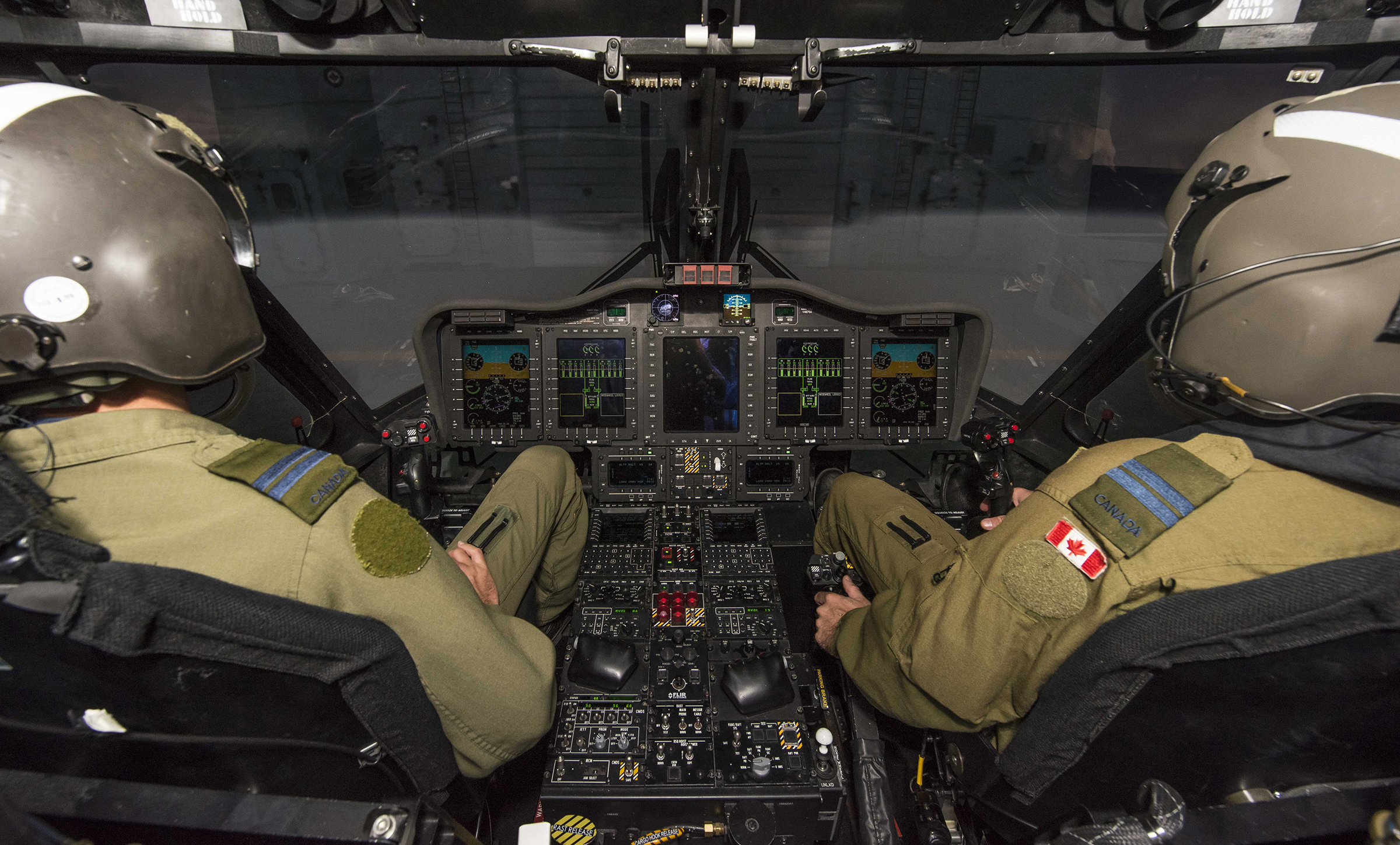 Two people wearing helmets and flight suits sit with their backs to the camera facing an aircraft control panel and aircraft windows.