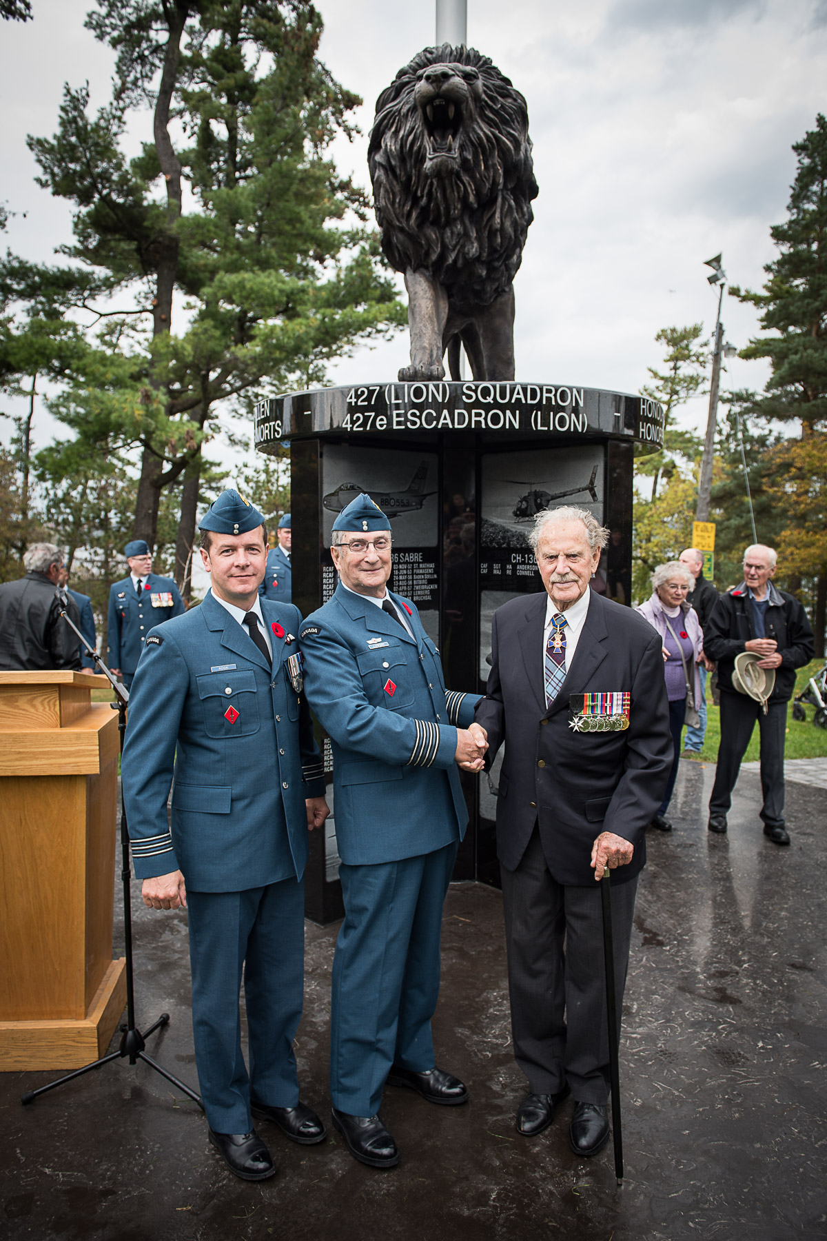 Two men in blue uniforms and an older man in a darker blue suit, all wearing medals, stand in front of a black monument topped with a statue of a roaring lion.