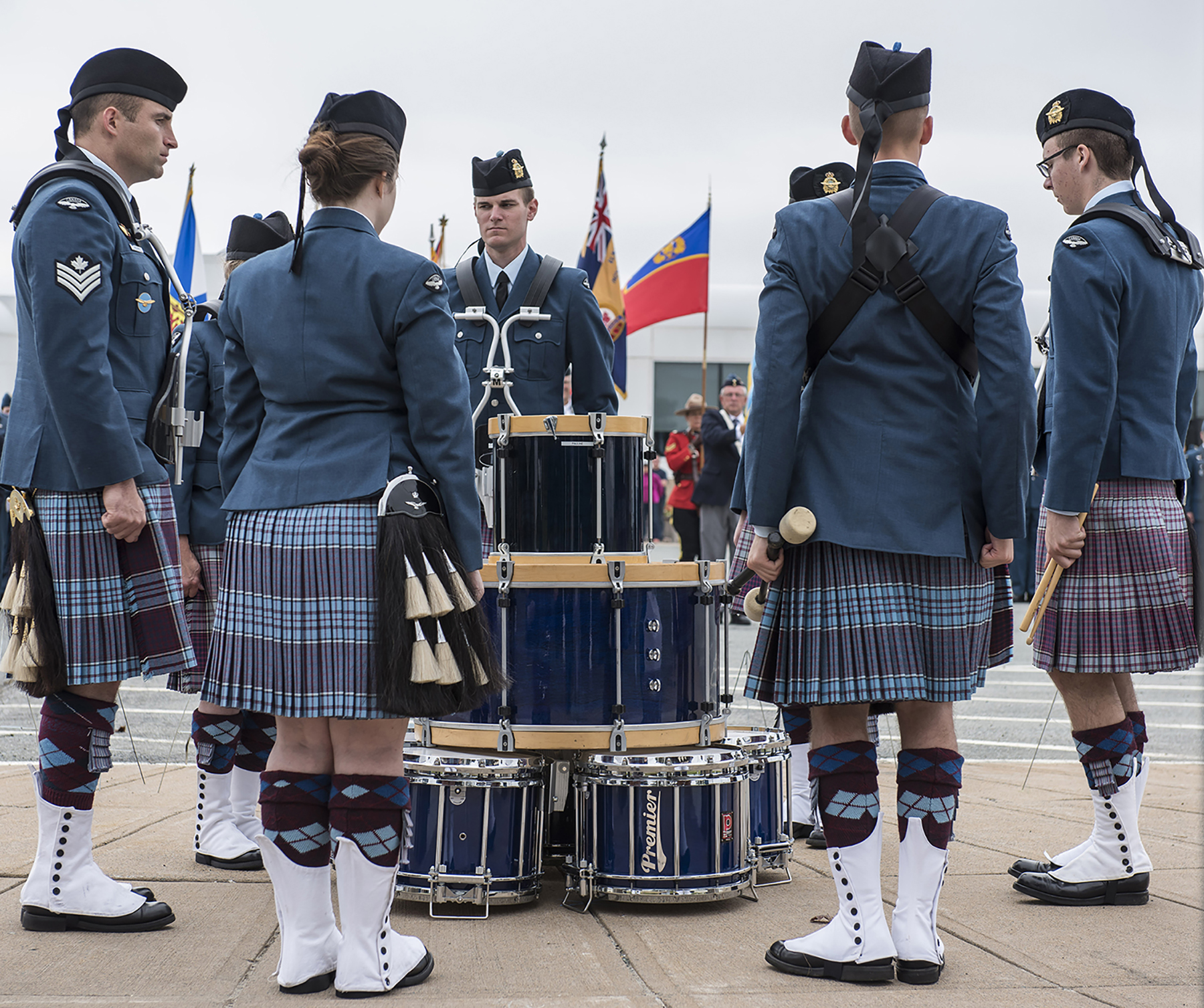 From left, clockwise, 12 Wing Pipes and Drums members Sergeant Marc Maloney, Major (retired) Pauline Quaghbeur, Sub-Lieutenant Jeremy Gaulin, Krista McLellan, Matthew Orlando, Aviator Keenan Weaver, and Beth MacDonald form a circle around their stacked drums in preparation for the September 17, 2017, Battle of Britain ceremony held at 12 Wing Shearwater, Nova Scotia. PHOTO: Corporal Anthony Laviolette, SW04-2017-0250-014