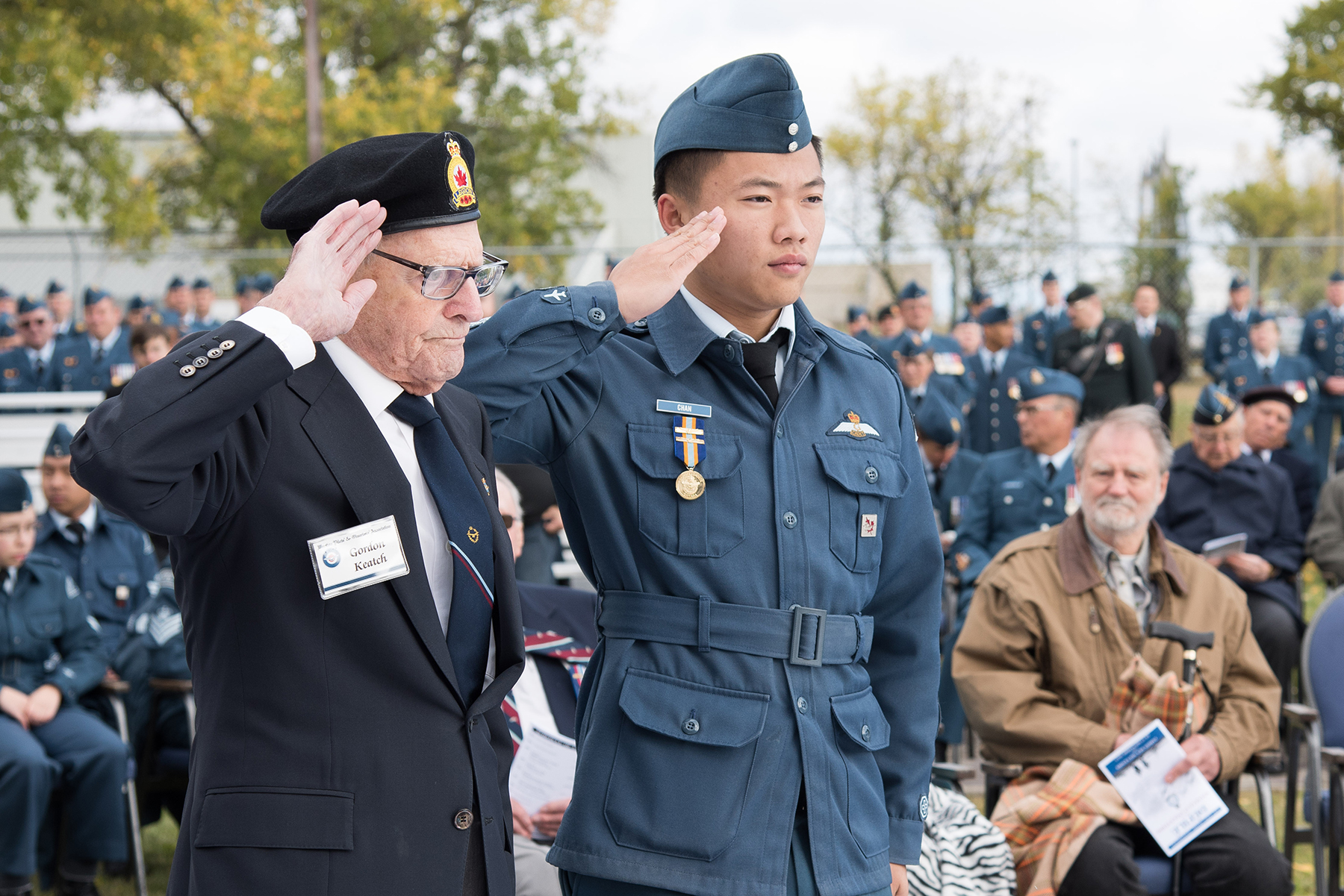 Royal Australian Air Force Flying Officer (retired) Gordon Keatch, accompanied by Royal Canadian Air Cadet Warrant Officer 1st Class Anson Chan, salutes after laying a wreath during the Battle of Britain parade on September 17, 2017, in the Garden of Memories at 17 Wing Winnipeg, Manitoba. PHOTO: Corporal Justin Ancelin, WG-2017-0337-044