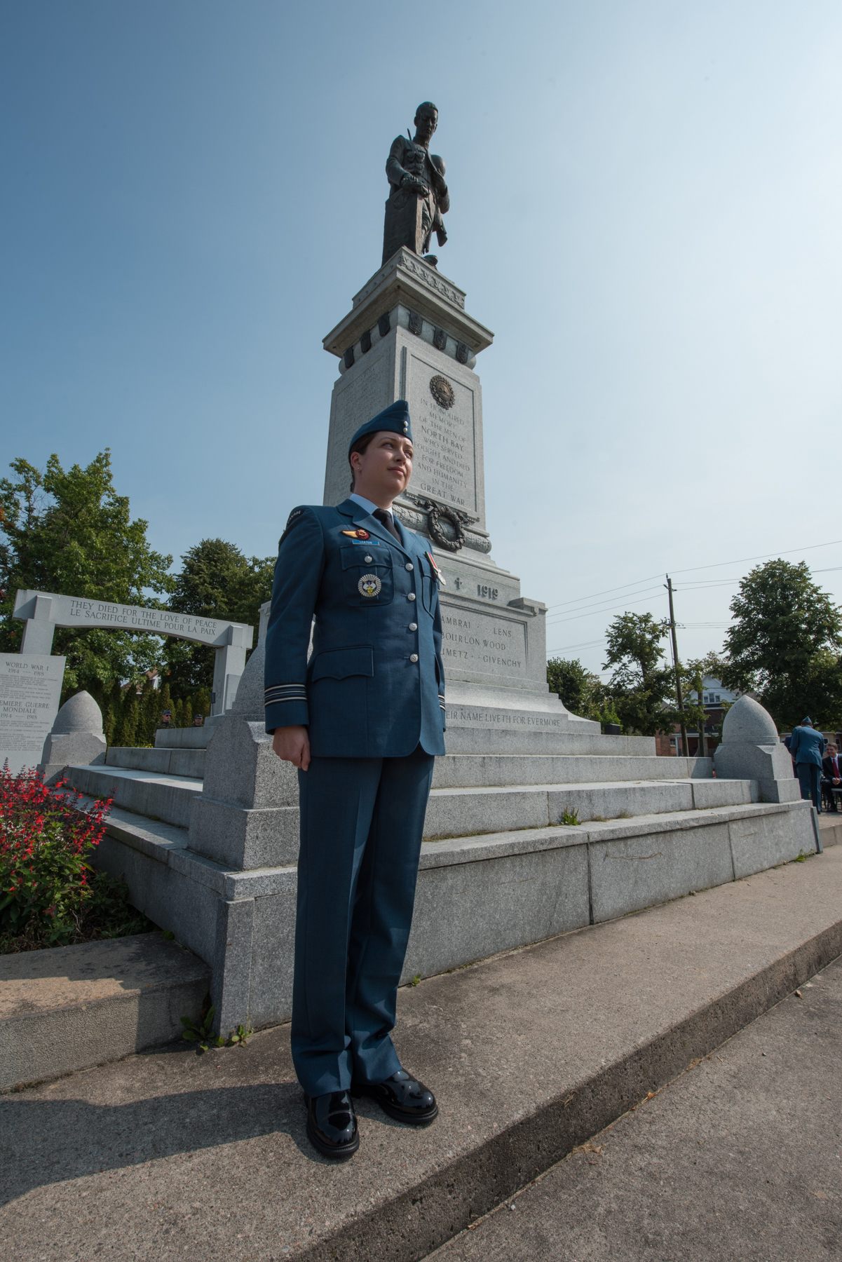 A woman wearing a medium-blue uniform stands at attention at the right front corner of a tall memorial topped with a statue and backed by trees.