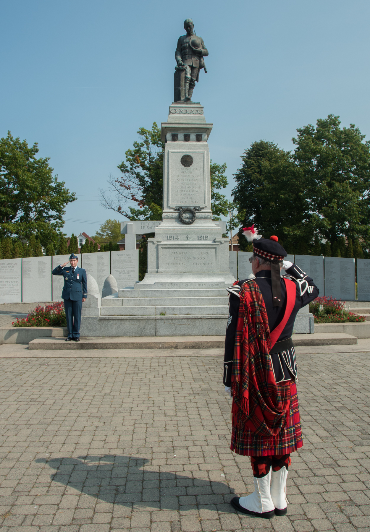 "Colours commander Jim Thompson (foreground), of Royal Canadian Legion Branch #23, and Parade commander Major Kathleen Leaton salute while ""O Canada"" is played at the War Cenotaph during the annual Battle of Britain Ceremony at Royal Canadian Legion Branch 23 in North Bay, Ontario, on September 17, 2017. PHOTO: Corporal Joseph Morin, NB02-2017-0211-008"