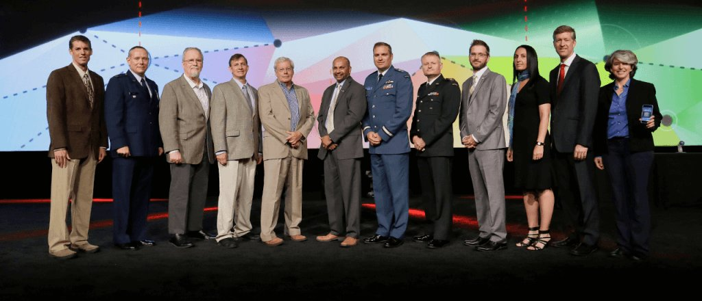 Then-Brigadier-General Blaise Frawley (sixth from the right, wearing an RCAF blue uniform) accepted the United States Geospatial Intelligence Foundation's military achievement award on behalf of the RCAF's Unclassified Remote-sensing Situational Awareness (URSA) system team. PHOTO: From the GSIF website