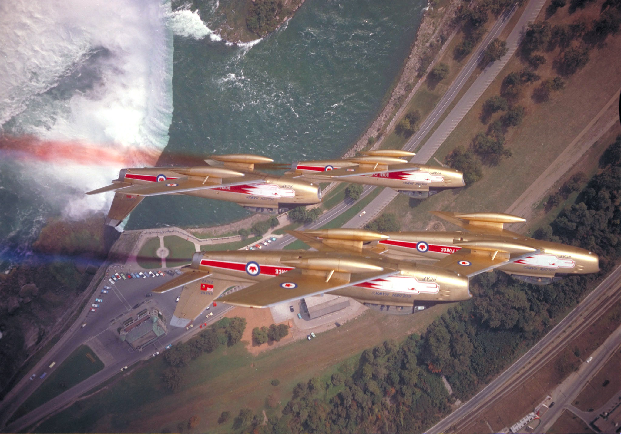 Four gold coloured aircraft in flight.
