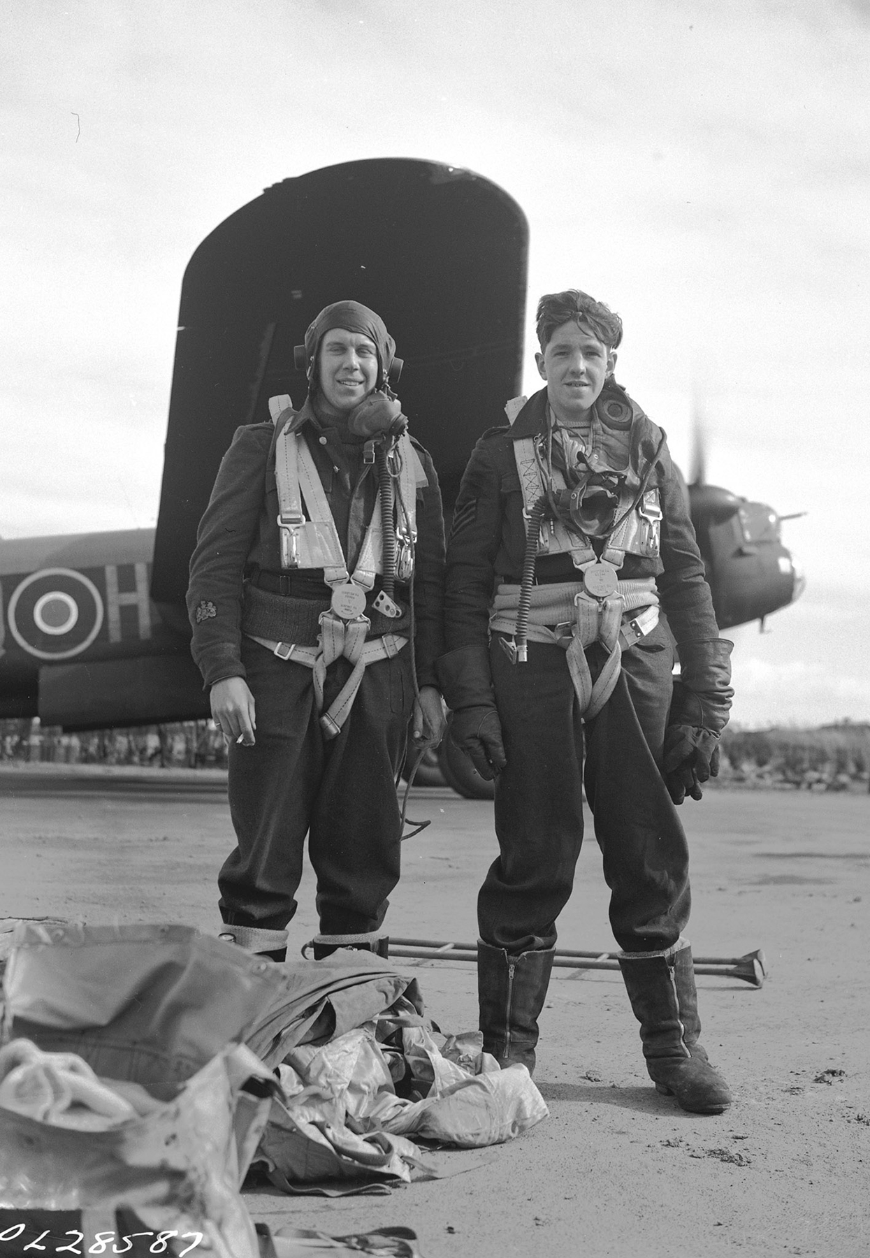 "The original caption of this photo reads: ""Fresh from the fray. These fliers of the 428 ""Goose"" Squadron in RCAF Bomber Group Overseas have just returned from a bombing raid over Frankfurt, Germany. Warrant Officer Arthur 'Mars' Marsden (left), a wireless air gunner from Montreal, Québec, and Sergeant George Harvey, a British rear gunner, saw a number of enemy fighters, and their aircraft was attacked twice: the first Nazi night fighter was identified as a Mello; the second fighter raced in, fired and was away so fast it could not be identified."" PHOTO: DND Archives, PL- 28587"