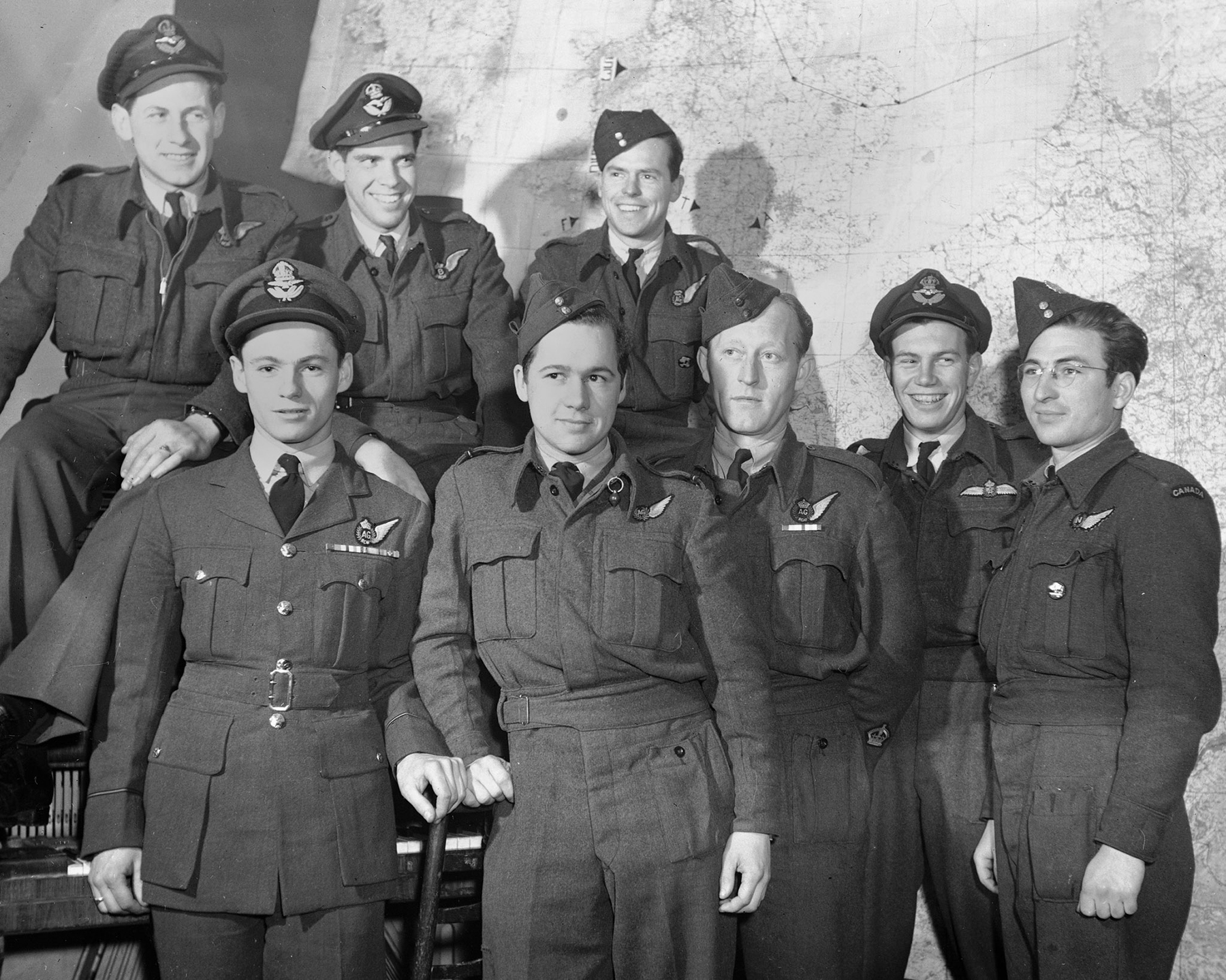 On November 24, 1945, at Leeming, England, the Bison and Lion Squadrons, are the only two Canadian bomber squadrons still flying with the Occupational Air Force. Pictured here, grouped in front of a large map, are 429 Bison Squadron men from Northern Ontario just before preparing for a flight to gather up RCAF men from the continent and bring them back to England. Front row, from left: Pilot Officer H.G. Bowles, Flying Officer D.M. Draper, Warrant Officer A.J. Wilvers, Flying Officer D.W. Greiger, and Flight Sergeant L.P. Gatien. Back row, from left: Flying Officer N.E. Beauchesne, Pilot Officer G.F. Burmaster, and Warrant Officer A.N. Boswell. PHOTO: DND Archives, PL-46308
