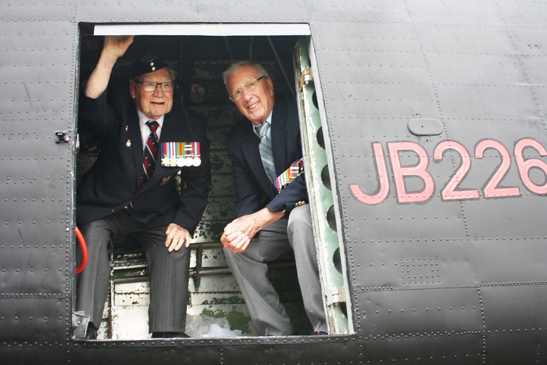 Two elderly men wearing medals on their blazers peer out of a vintage aircraft with riveted skin and bearing the designation JB266.