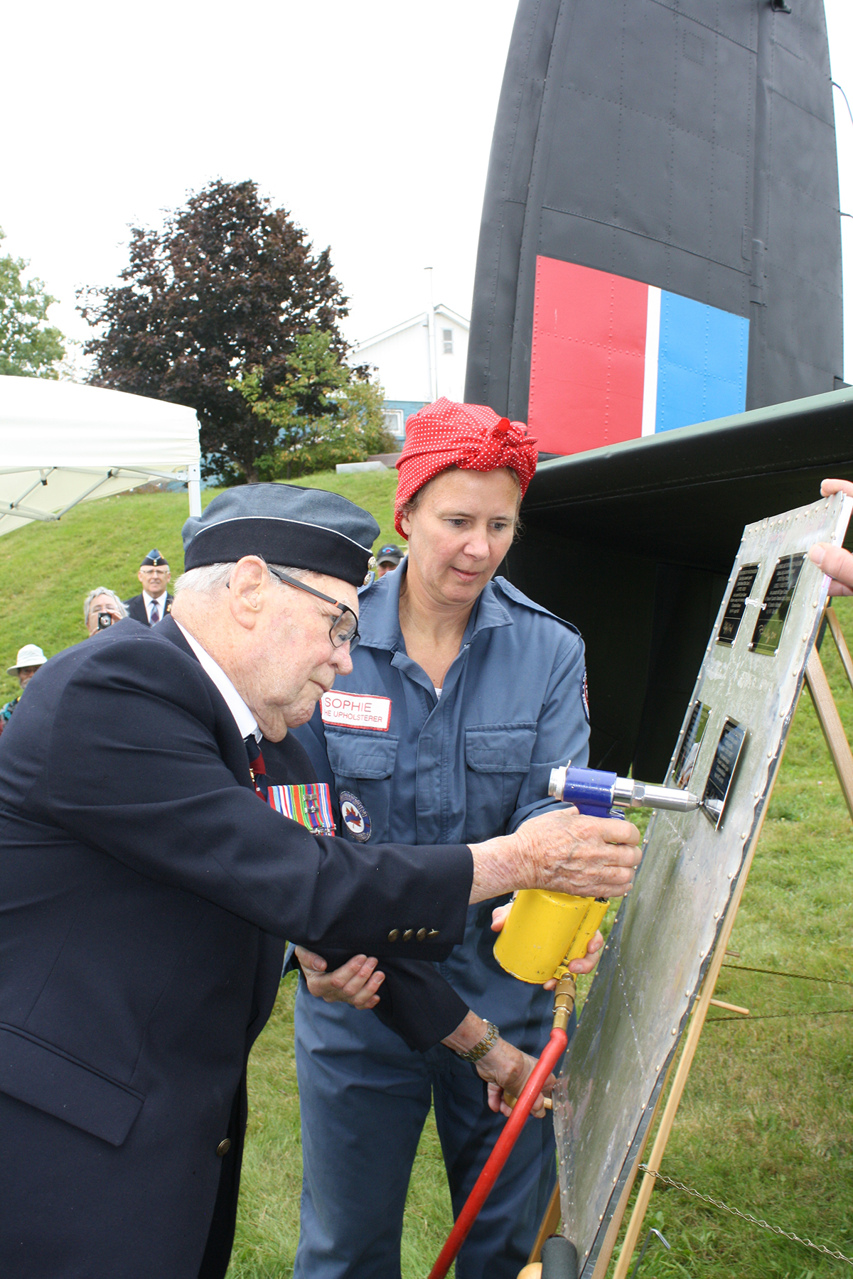 "Museum volunteer Sophie Saulnier assists Flying Officer (retired) Henry ""Chick"" Hewitt as he rivets his personalized memorial plaque into place. The marker will be permanently placed inside the Greenwood Military Museum's restored Lancaster bomber JB226 where Flying Officer Hewitt served as a navigator during the Second World War. PHOTO: Sara Keddy"
