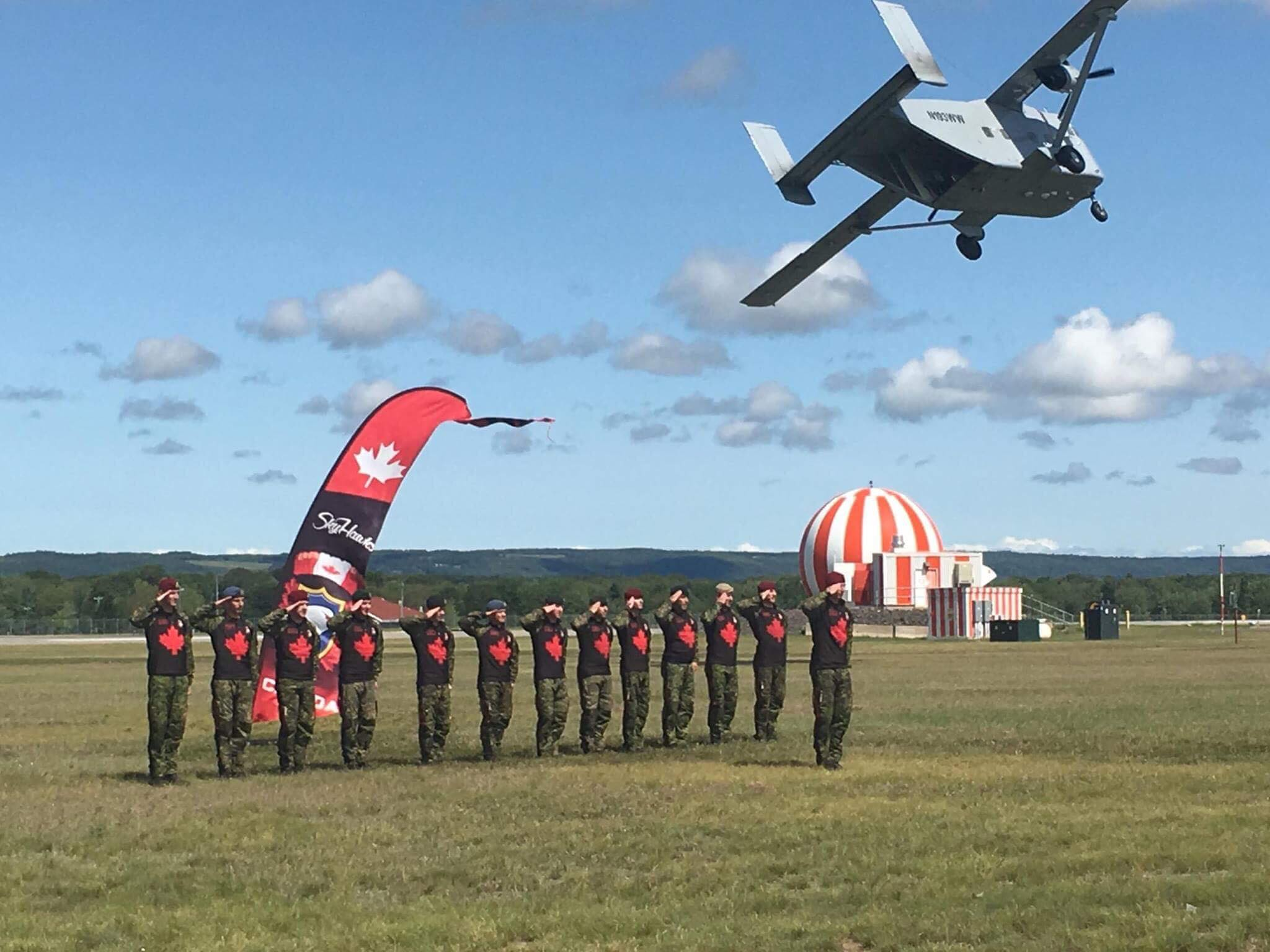 "The SkyHawks line up for the ""salute line"" as their jump aircraft, the SkyVan, makes a low pass at the end of their performance during the Atlantic Canada International Air Show at 14 Wing Greenwood, Nova Scotia, in late August 2017. PHOTO: Via SkyHawks Facebook page"
