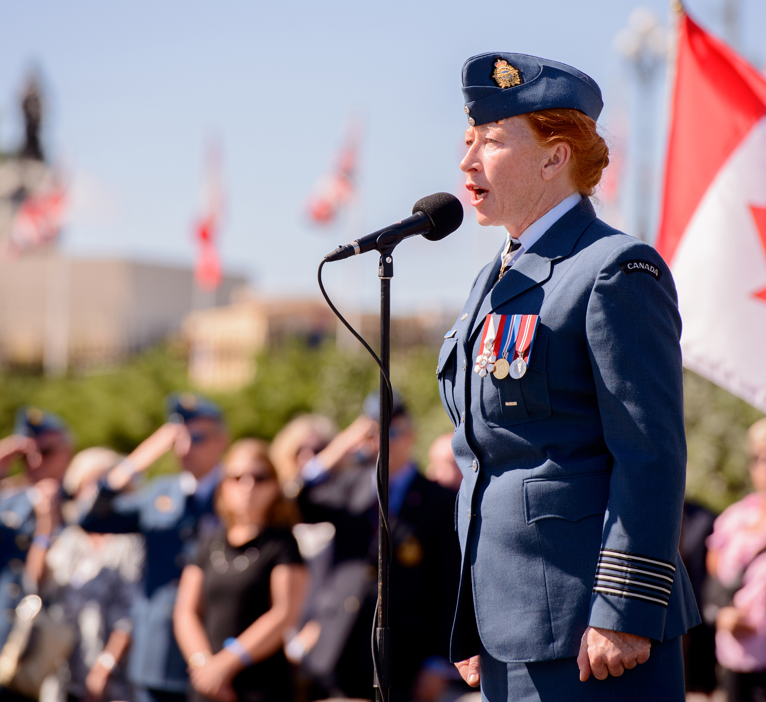 "The RCAF's Honorary Colonel Loreena McKinnett sings ""O Canada"" during the national ceremony marking the 75th anniversary of the Battle of Britain, held on Parliament Hill in Ottawa on September 20, 2015. The internationally renowned singer-songwriter has released ""Breaking the Sword"", a new single about love, dedication and family sacrifice, in time for Remembrance Day. PHOTO: Master Corporal Daniel Merrell, SU03-2015-0736-078"