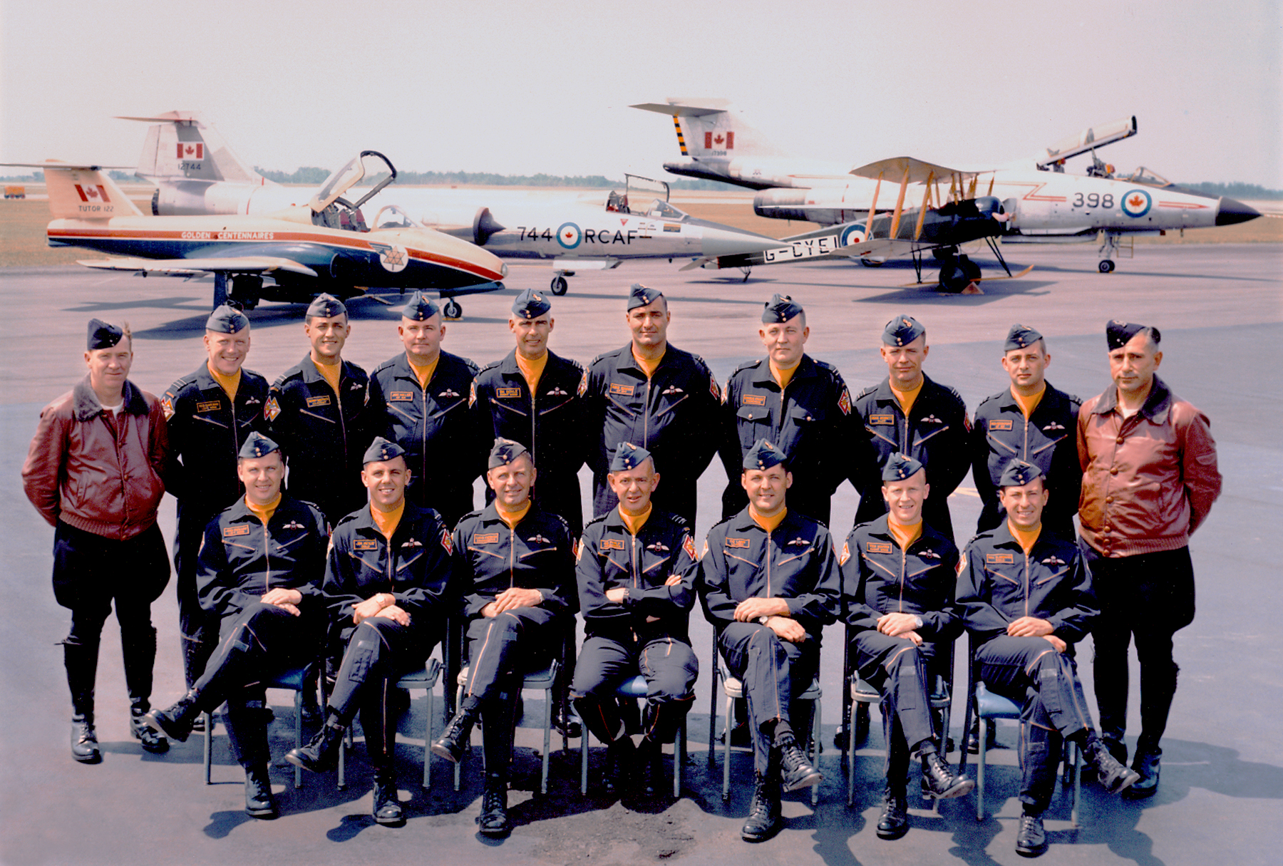 The 1967 Golden Centennaires officers. Front row, from left, are Flight Lieutenant John Swallow (left wing), Flying Officer Jim McKay (opposing solo), Squadron Leader Lloyd Hubbard (public information officer), Wing Commander O.B. Philp (commanding officer), Squadron Leader C.B. Lang (team leader), Flight Lieutenant Tom Hinton (right wing), and Flight Lieutenant Bill Slaughter (lead solo). Back row, from left, are Flight Lieutenant Gord Brown (Avro 504K), Squadron Leader Bob Dagenais (outer left wing), Flight Lieutenant Denis Gauthier (commentator), Flight Lieutenant Jake Miller (CF-101), Squadron Leader B.K. Doyle (outer right wing), Flight Lieutenant René Serrao (CF-104), Flight Lieutenant Charlie Grant (engineering officer), Squadron Leader Russ Bennett (slot), Flight Lieutenant Rob McGimpsey (CF-101 navigator), Flight Lieutenant George Greff (Avro 504K). Missing are Flight Lieutenant Jack Waters (the Red Knight,), and his alternate, Flying Officer Rod Ellis. In the background are, from left, a Centennaire CT-114 Tutor, a CF-104 Starfighter, an Avro 504K, and a CF-101 Voodoo. PHOTO: DND, Corporal Bob Imre