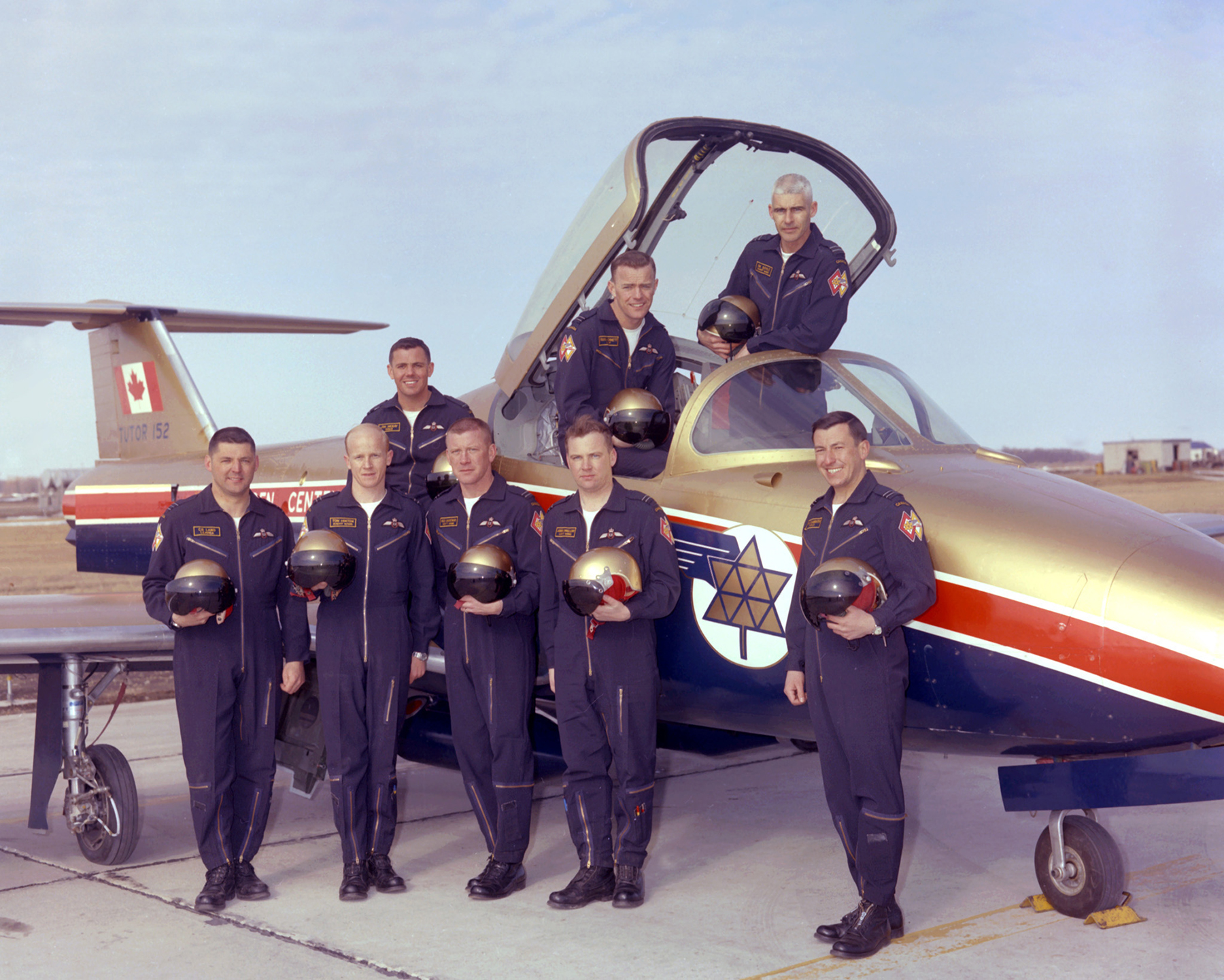 The Golden Centennaires Tutor pilots in Portage la Prairie, Manitoba, on April 6, 1967. Front, from left: Squadron Leader Clarence Lang, Flight Lieutenant Tom Hinton, Flight Lieutenant Red Dagenais, Flight Lieutenant John Swallow, and Flight Lieutenant Bill Slaughter, Back, from left:  Flying Officer Jim McKay, Flight Lieutenant Russ Bennett, and Flight Lieutenant B.K. Doyle. Flight Lieutenants Bennett and Doyle were promoted to squadron leader before the start of the season PHOTO: DND Archives, WG67-104-3