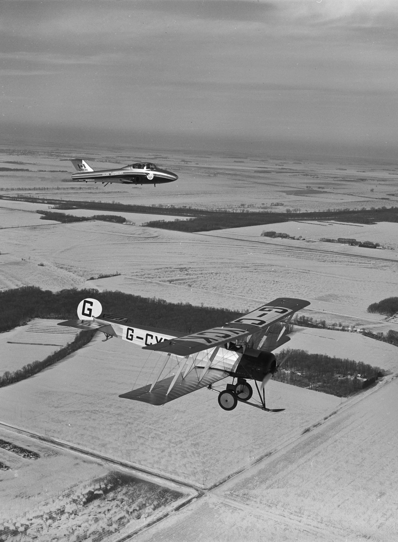 In 1967, two Golden Centennaires aircraft, an Avro 504K biplane (foreground) and a CT-114 Tutor, overfly the prairies of Western Canada. PHOTO: DND Archives, CF67-167-10