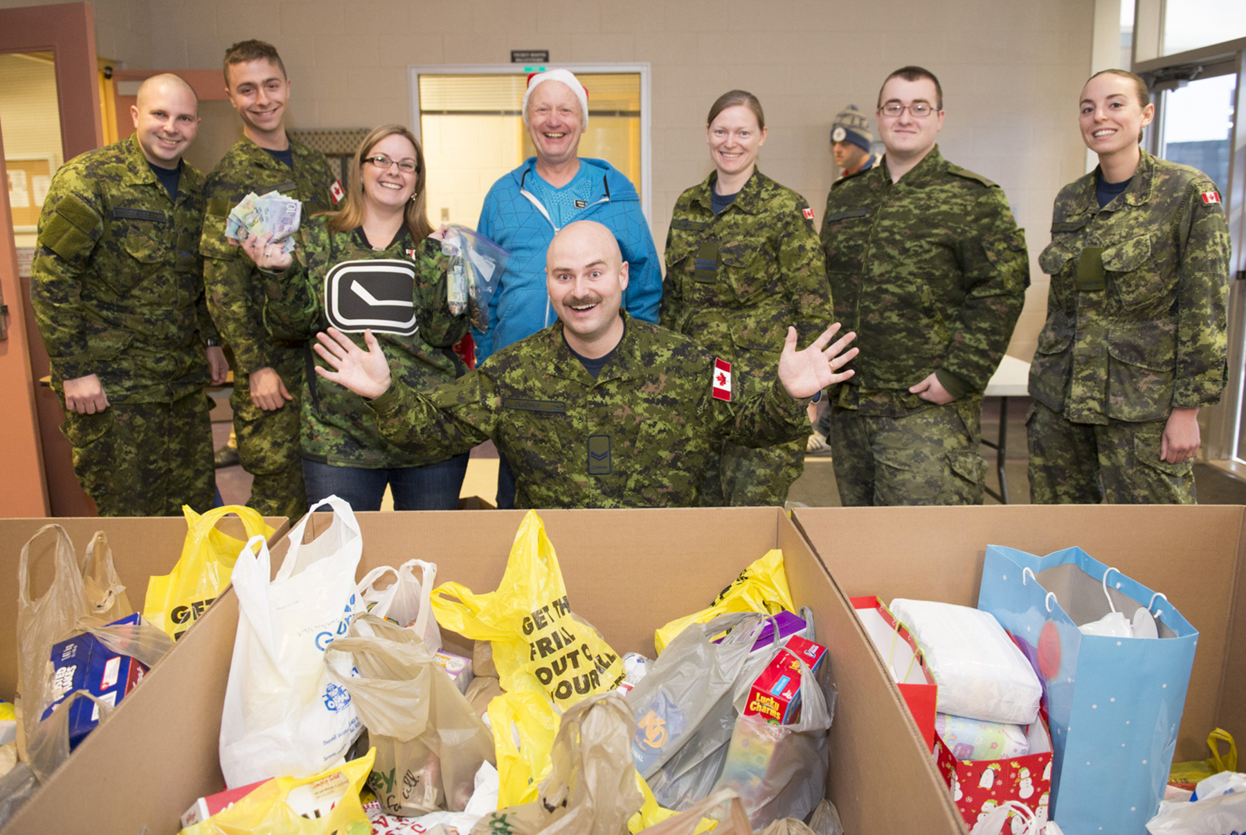 Six people wearing disruptive pattern uniforms and one civilian, stand behind a man, also wearing a disruptive pattern uniform, who is gesturing at cardboard boxes filled with bags of foodstuffs.