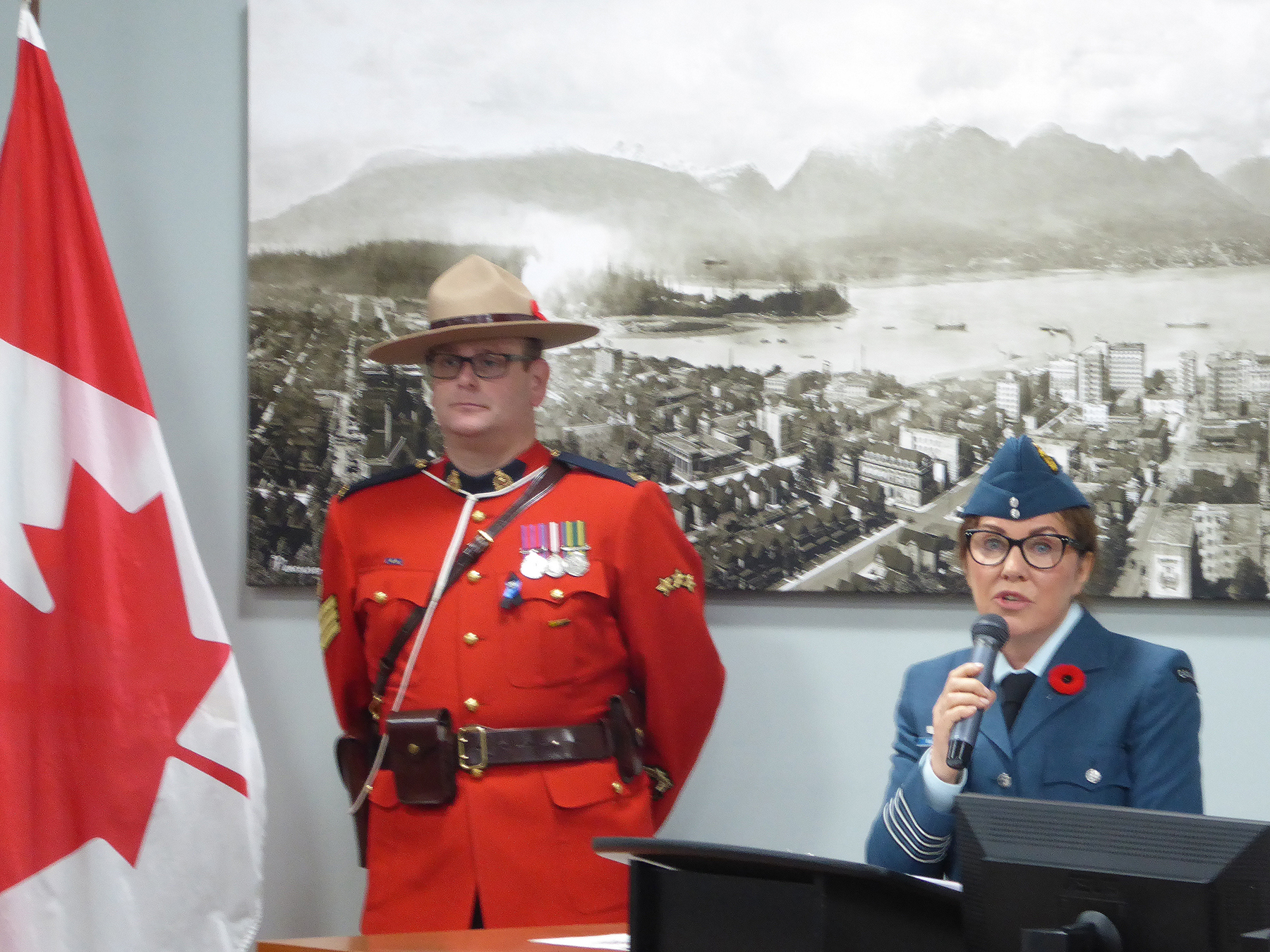 Overseen by Sergeant Chad Greig of the Royal Canadian Mounted Police, Honorary Colonel Diane McCurdy, of 442 Transport and Rescue Squadron, addresses new citizens and attendees during one of two November 7, 2017, remembrance-themed citizenship ceremonies held in Surrey, British Columbia. PHOTO: Submitted