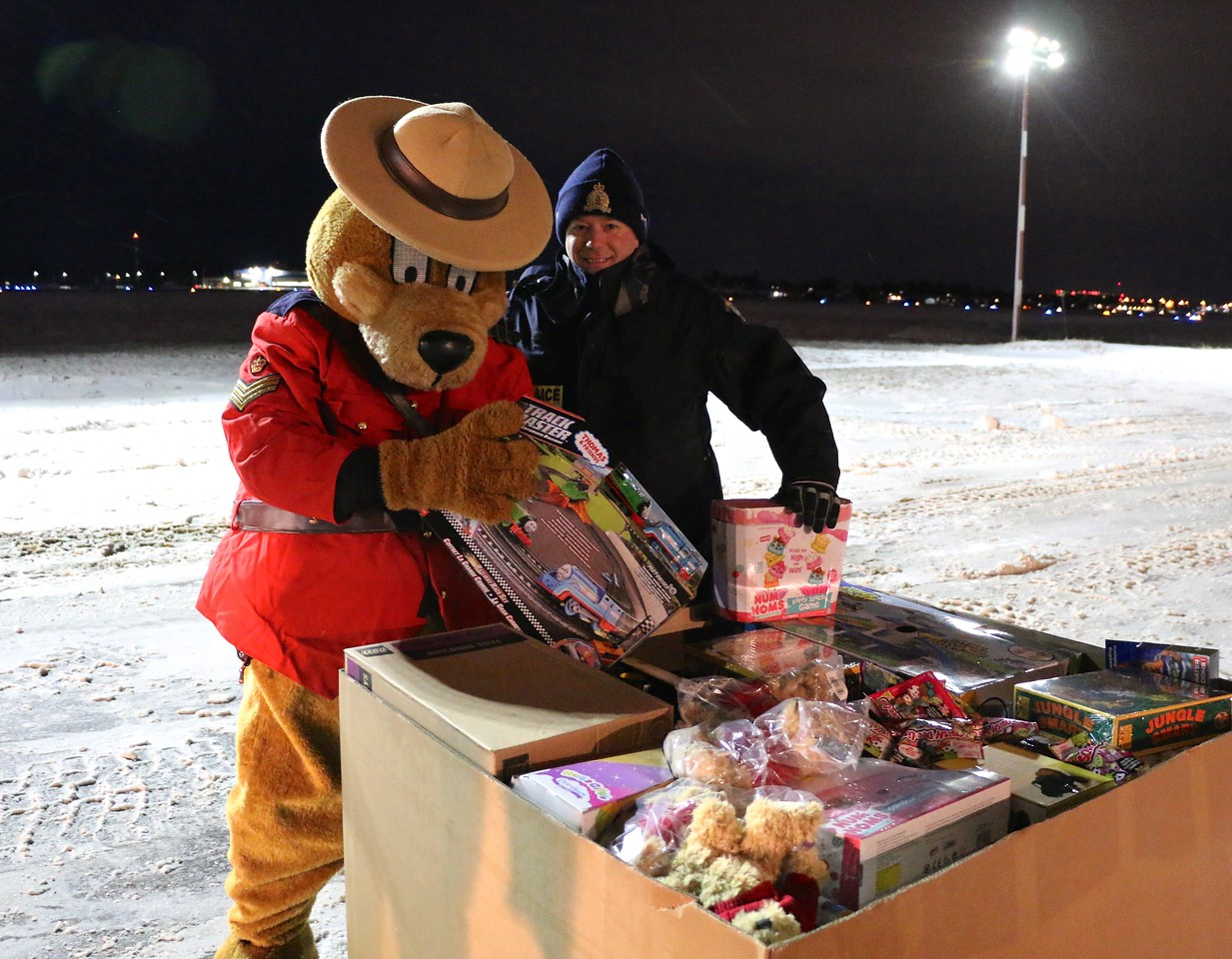 A person in a large bear mascot costume wearing an RCMP uniform and a person wearing a military uniform look at toys packed in a waist-high cardboard box.