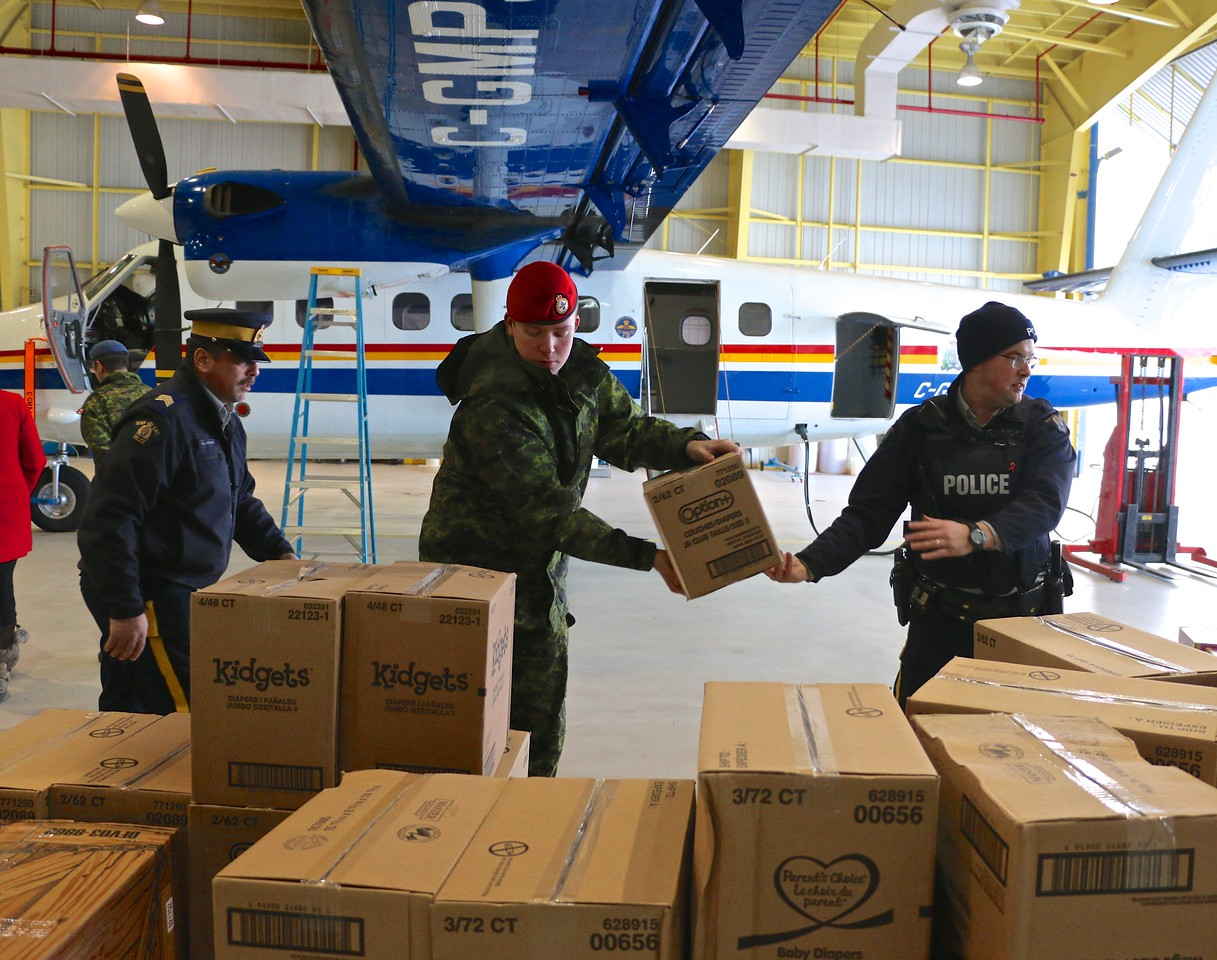 Personnel from 5 Wing Goose Bay, Newfoundland and Labrador, and the Happy Valley-Goose Bay Royal Canadian Mounted Police detachment unpack pallets of toys on December 7, 2017. PHOTO: Makala Chapman