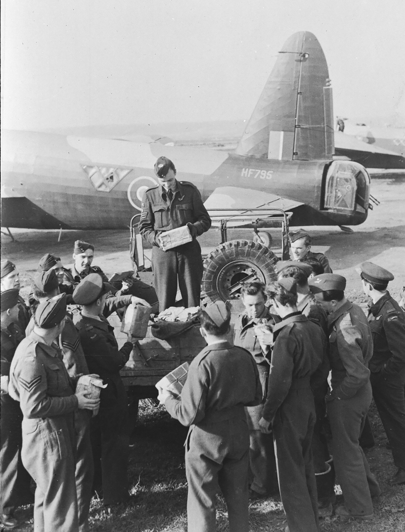 RCAF aircrew and groundcrew cluster around a truck at a North African airfield to get their Christmas mail and parcels that have been flown from Canada to North Africa via the UK by Flying Fortresses of the RCAF Air Transport Command. PHOTO: DND Archives, PL-18693