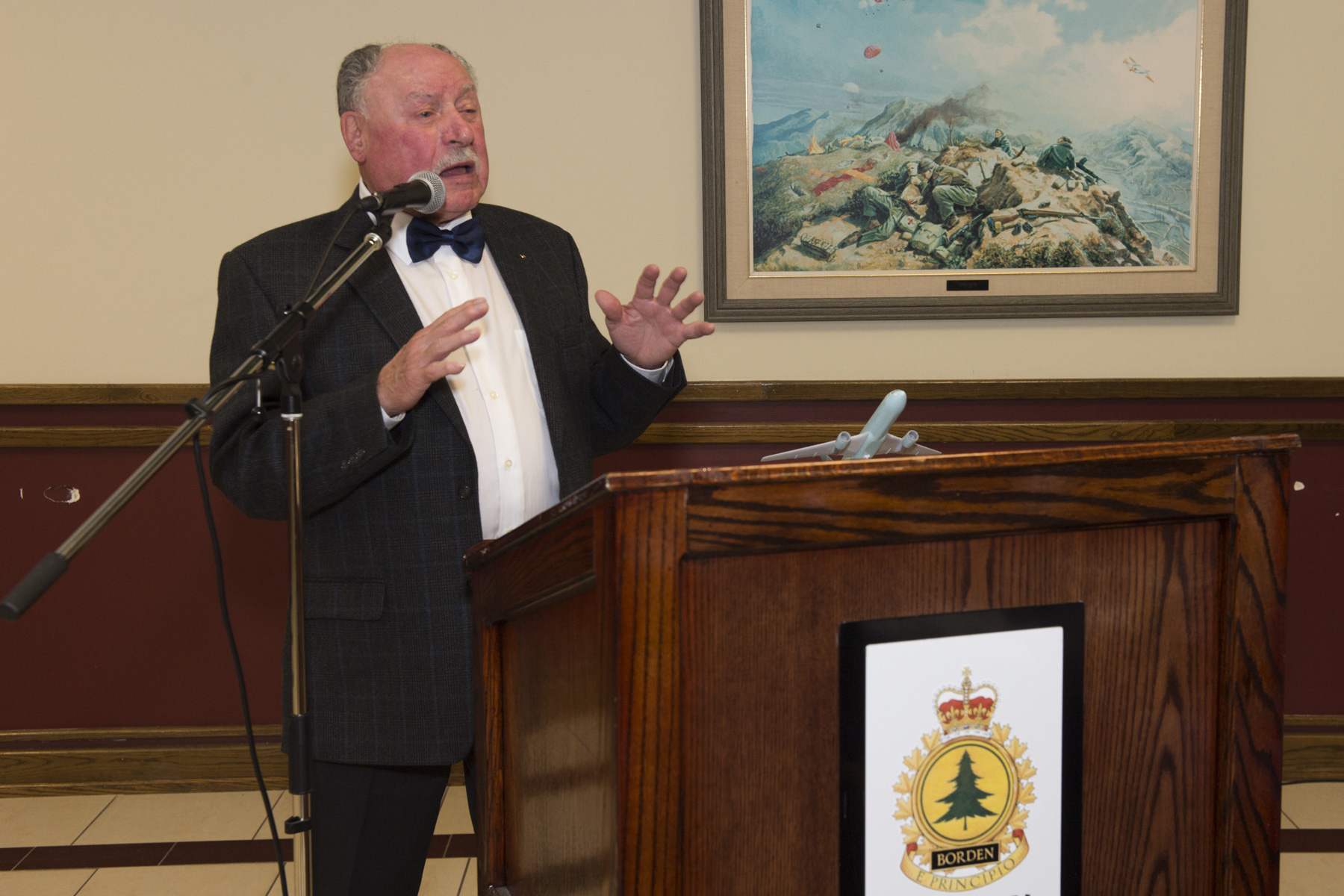 A man in a dinner jacket stands at a podium and speaks into a microphone bearing a model of a passenger aircraft. Behind him is a painting of soldiers on a hilltop during a battle.