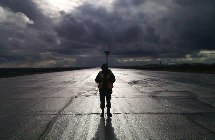 A person wearing a reflective vest and standing in moonlight on a runway holds a tall stick with something mushroom-shaped, with small reflective flags, on top.