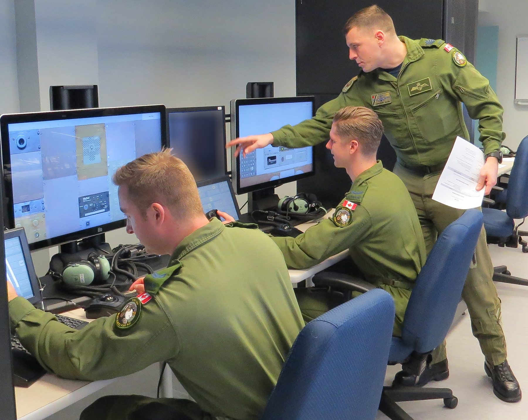 Two men in olive green uniforms sit at computer stations while a third man, wearing a similar uniform and holding some paper, points toward one of the screens.