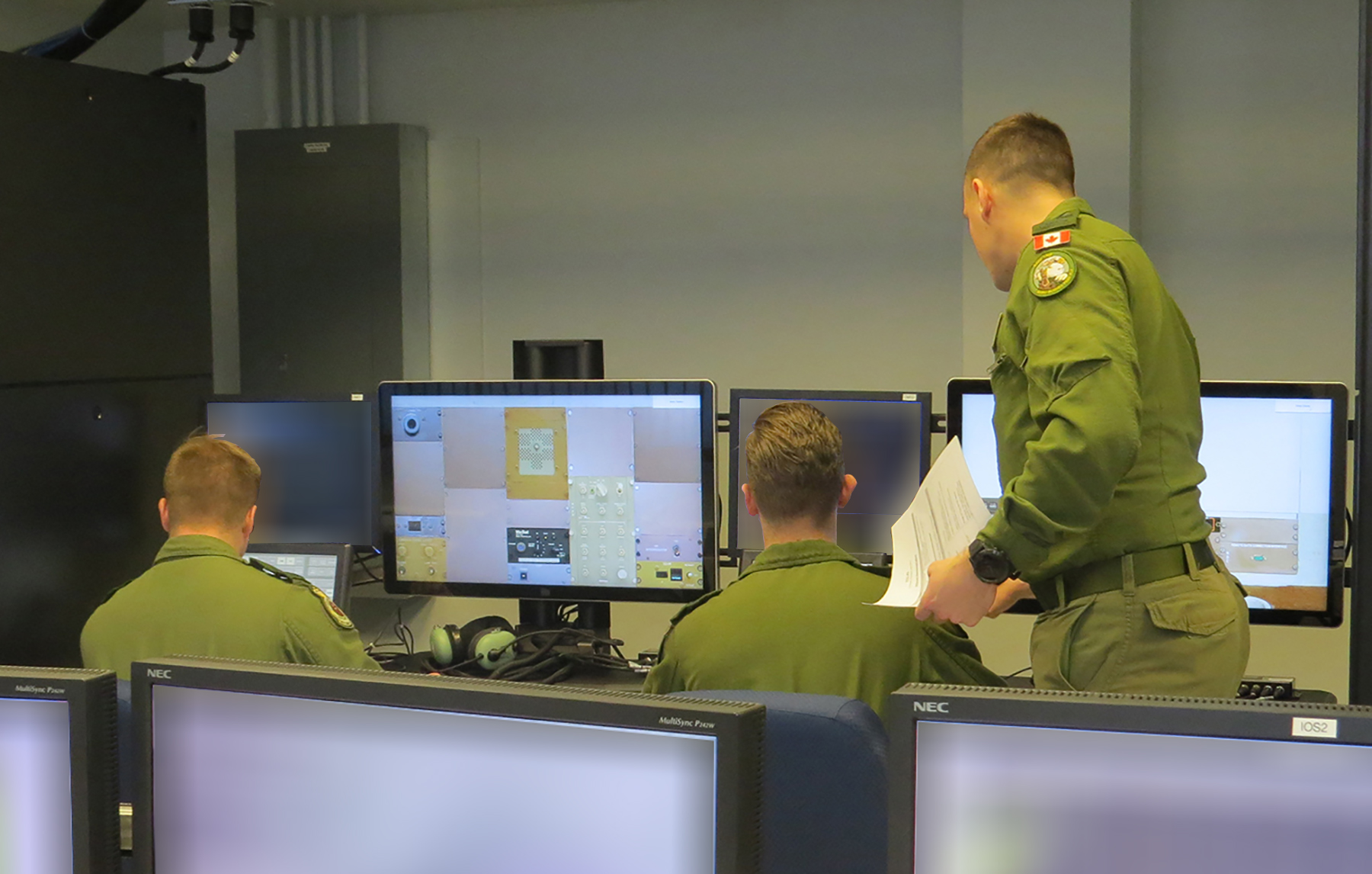 Corporal Matthew Denis (left) and Corporal Connor Slaunwhite work on the Procedural Crew Trainer System at 402 Squadron, under the tutelage of Sergeant Spencer Cass. PHOTO: Officer Cadet Kylie Penney