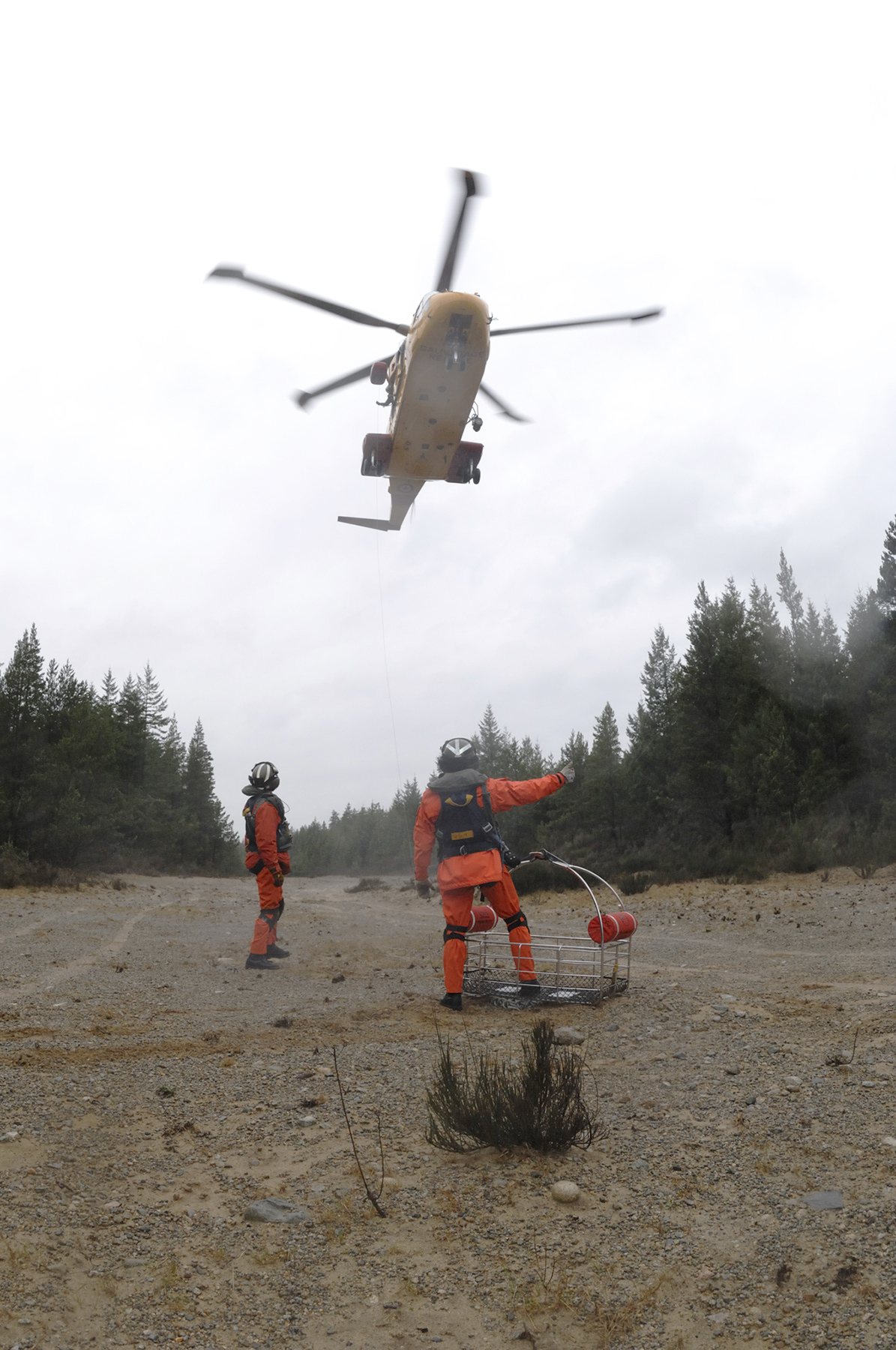 Search and rescue (SAR) technicians Corporal Martin Tessier and Sergeant Wayde Simpson prepare to send a SAR basket up to a CH-149 Cormorant helicopter during a Cormorant training exercise on Savry Island, British Columbia, on February 14, 2007. PHOTO:  Private Kelly Mitton, cx2007-0061-05