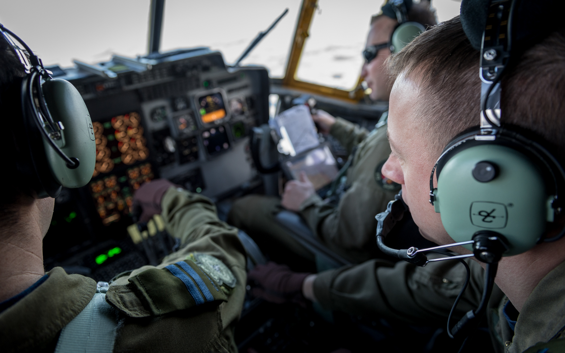 Flight engineer Sergeant Alex Cloutier (foreground, right) monitors aircraft systems. PHOTO: Corporal Neil Clarkson, GD05-2018-0060-016