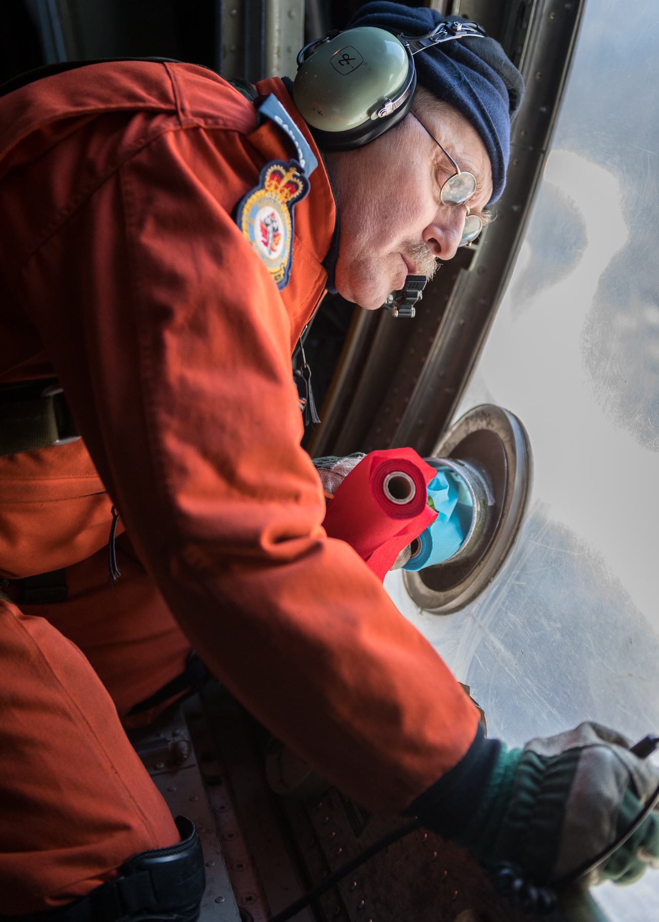 Sergeant André Hotton, a search and rescue technician, prepares to release marker streamers from a CC-130 Hercules aircraft. PHOTO: Corporal Neil Clarkson, GD05-2018-0060-029