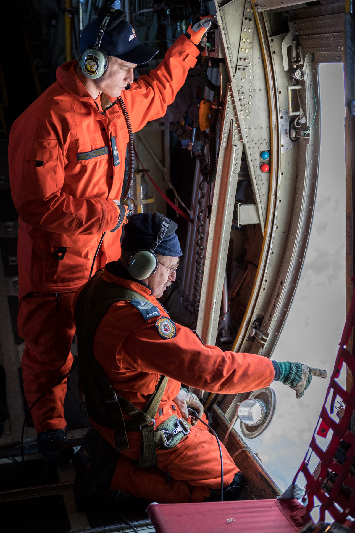 Search and rescue technicians Master Corporal Dylan Weller (standing) and Sergeant André Hotton track the descent of marker streamers from a CC-130 Hercules aircraft. PHOTO: Corporal Neil Clarkson, GD05-2018-0060-037