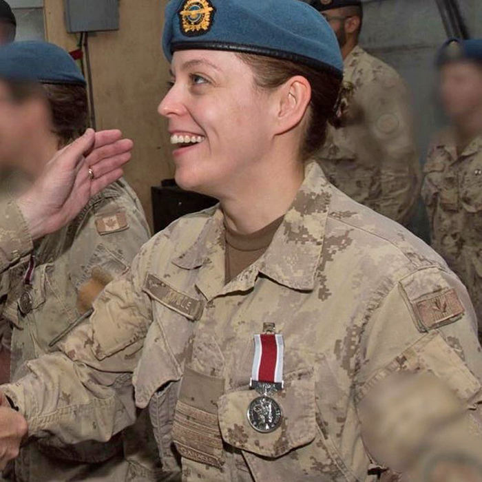 A smiling woman dressed in desert pattern camouflage uniform with a medal attached to the uniform jacket.