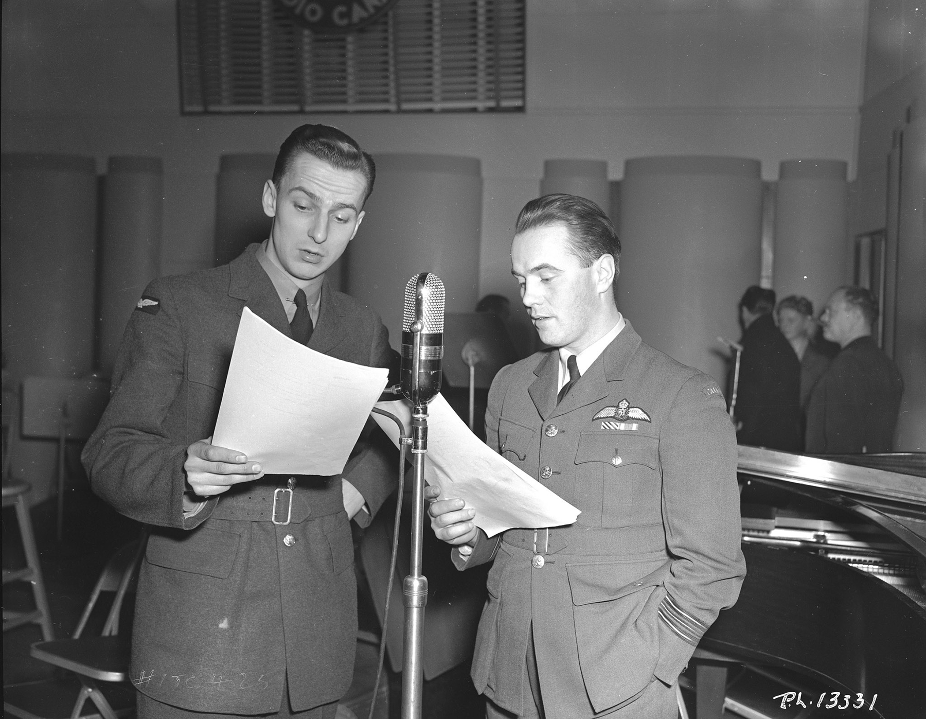 On February 14, 1943, Royal Canadian Air Force Distinguished Flying Cross recipient Squadron Leader Ken Boomer is interviewed by Aircraftman Second Class F. Markle during the recording of one of American comedian and radio star Jack Benny's regular Sunday night radio programs. This one was recorded in Toronto, Ontario, in front of a live audience comprising  RCAF and other Canadian Armed Forces members. PHOTO: DND Archives, PL-13331